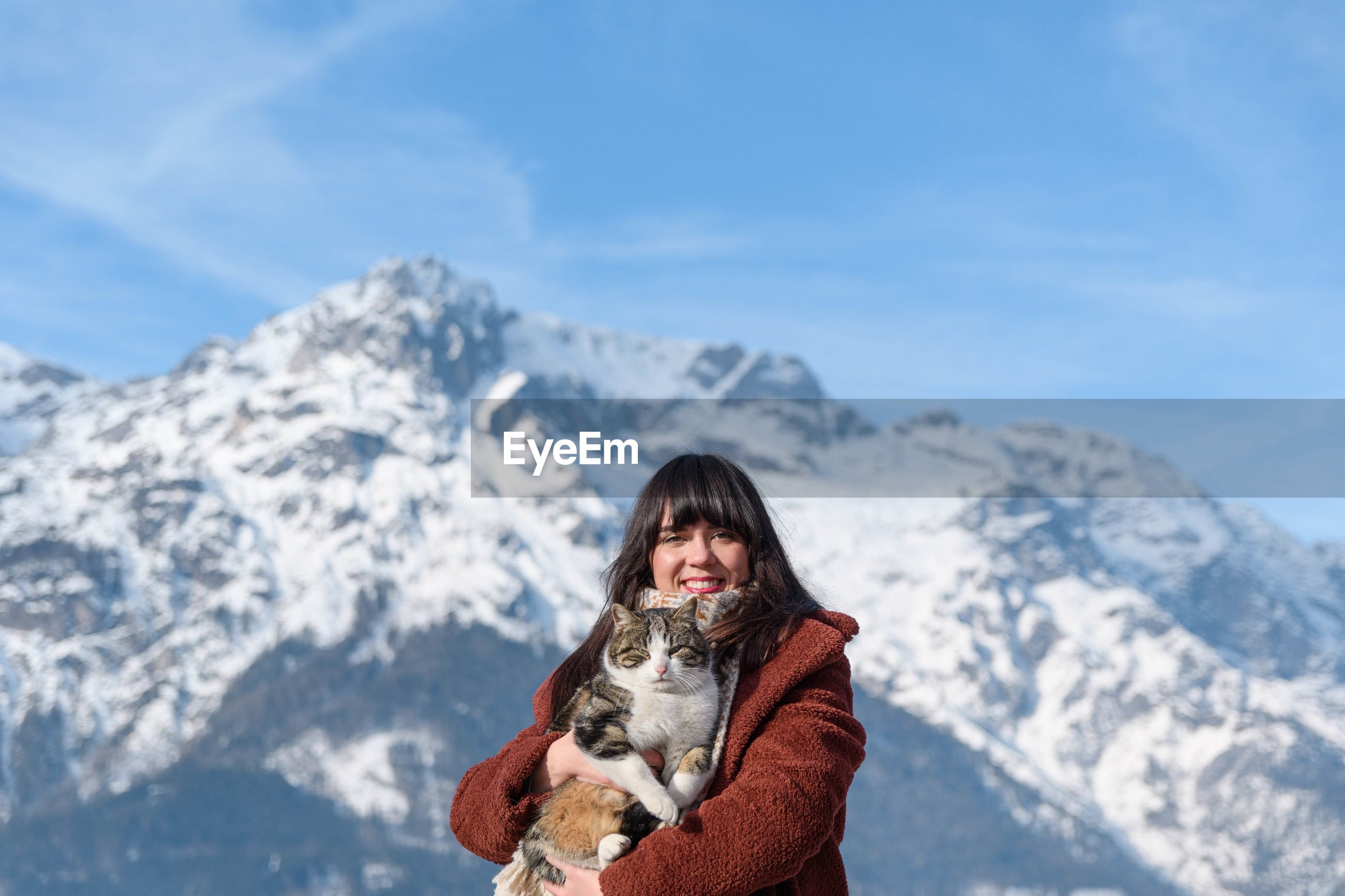 Portrait of a young woman holding a cat. mountains, winter, depth of field.