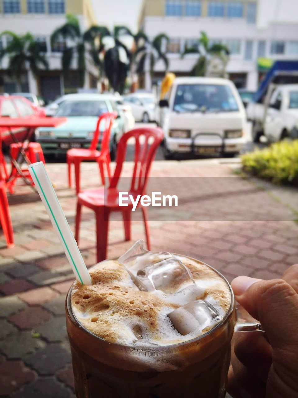 human body part, human hand, food and drink, coffee - drink, drink, coffee cup, focus on foreground, real people, outdoors, refreshment, day, one person, table, sidewalk cafe, cafe, disposable cup, close-up, iced coffee, food, holding, red, freshness, city, frothy drink, people