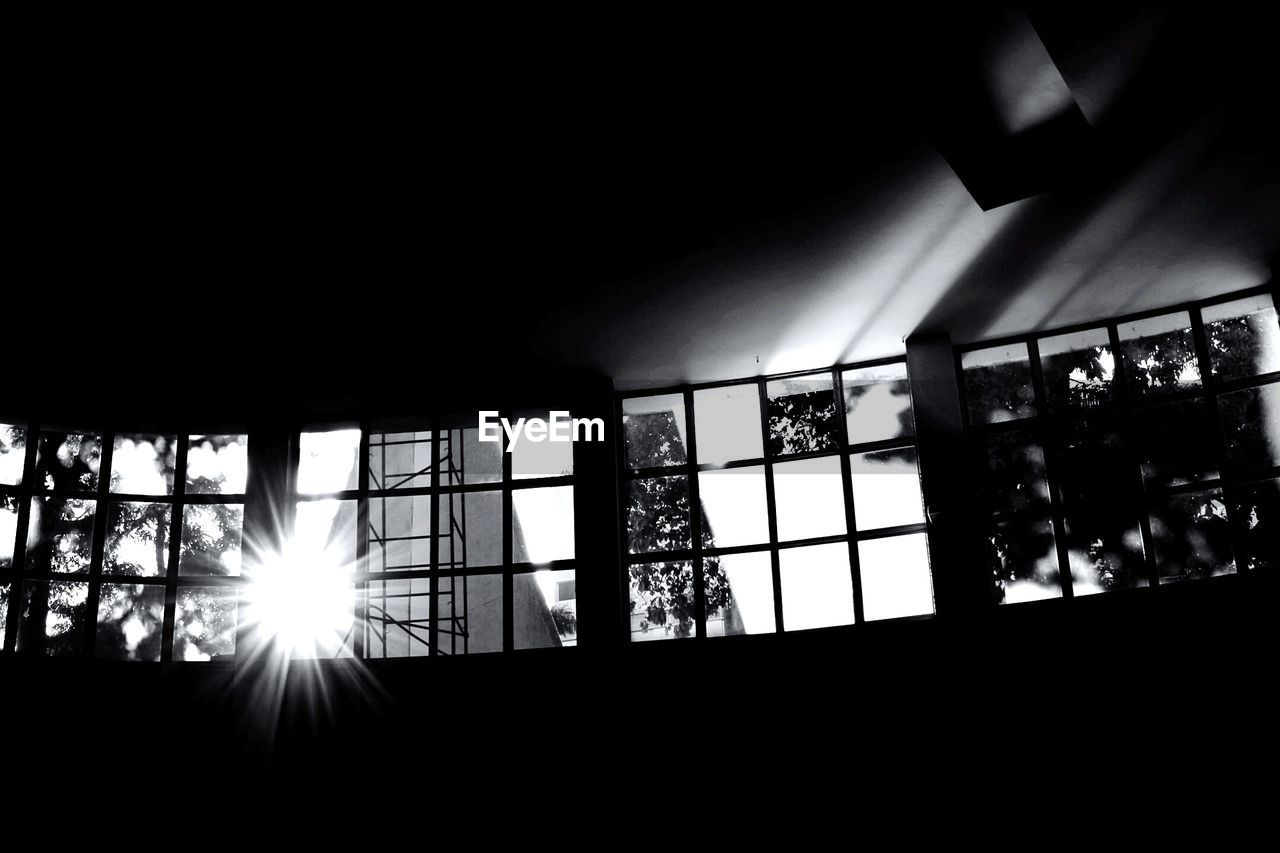 window, sunlight, indoors, no people, day, dark, nature, silhouette, architecture, low angle view, illuminated, sunbeam, built structure, lens flare, sun, copy space, glass - material, streaming, plant, ceiling, glass, brightly lit