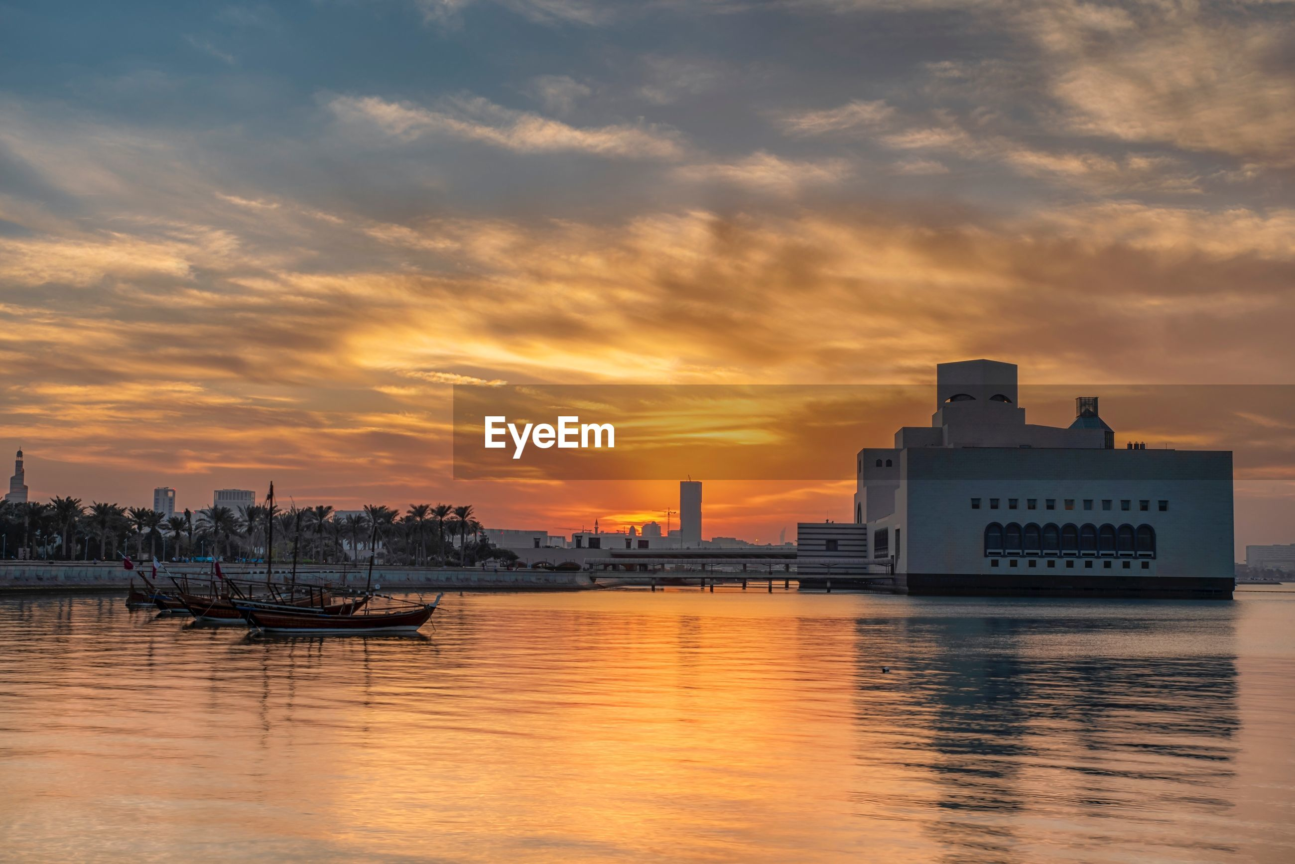 SCENIC VIEW OF RIVER BY CITY AGAINST ORANGE SKY
