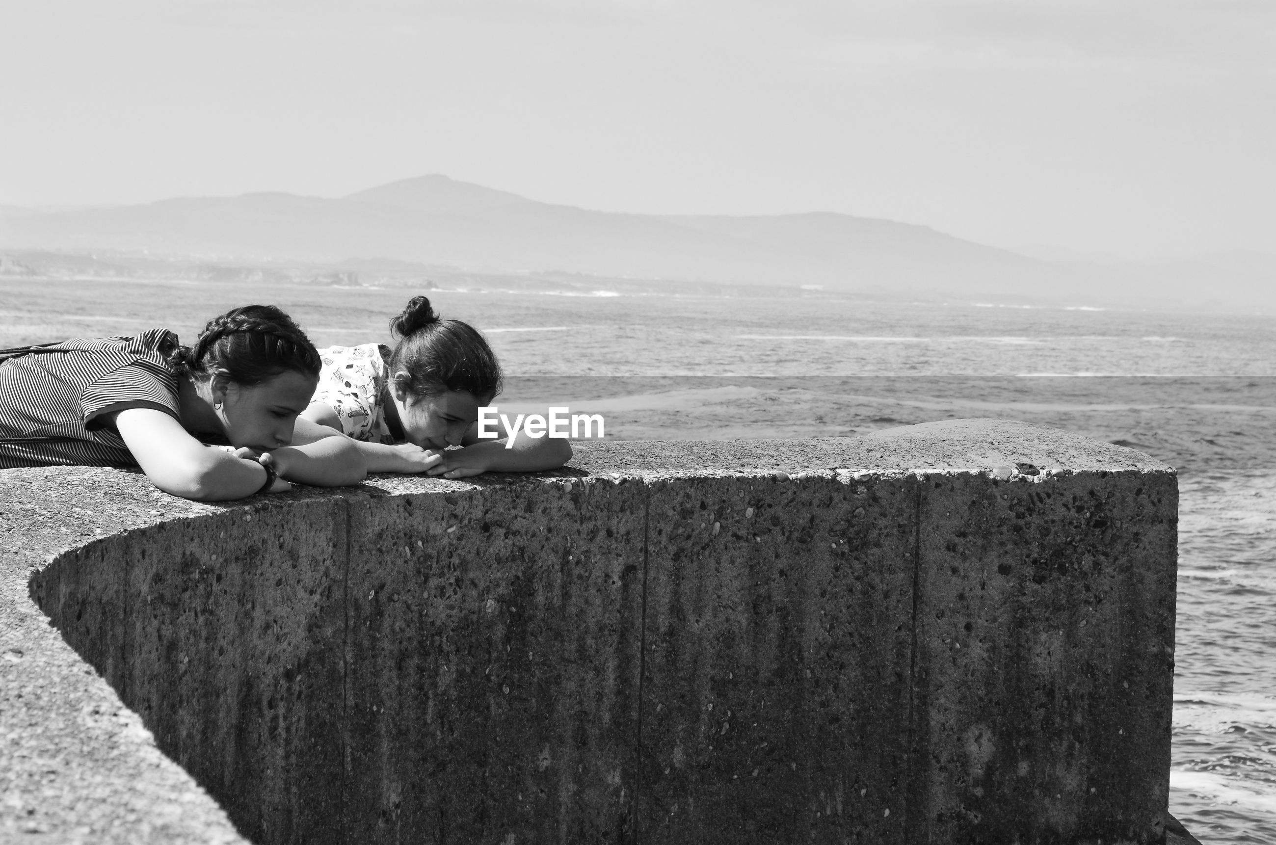 Friends leaning on wall by sea against sky