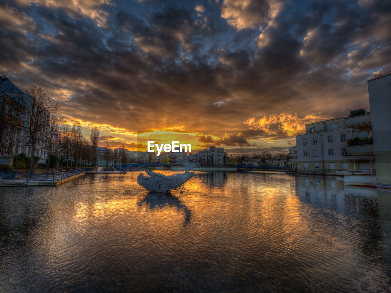 water, cloud - sky, sky, nautical vessel, building exterior, architecture, transportation, built structure, mode of transportation, sunset, reflection, nature, waterfront, city, beauty in nature, building, no people, orange color, outdoors, canal