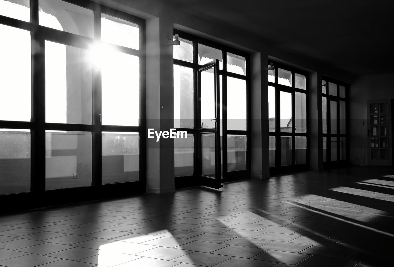 window, indoors, flooring, day, sunlight, architecture, built structure, building, no people, glass - material, empty, absence, wood, shadow, domestic room, entrance, transparent, door, tiled floor, window frame