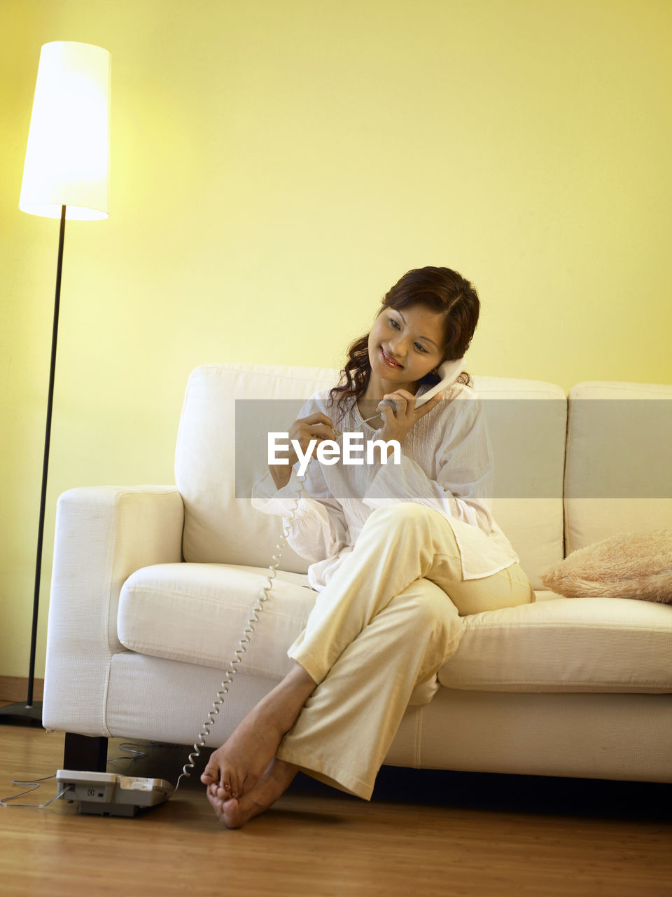 Smiling woman talking on telephone while sitting at home