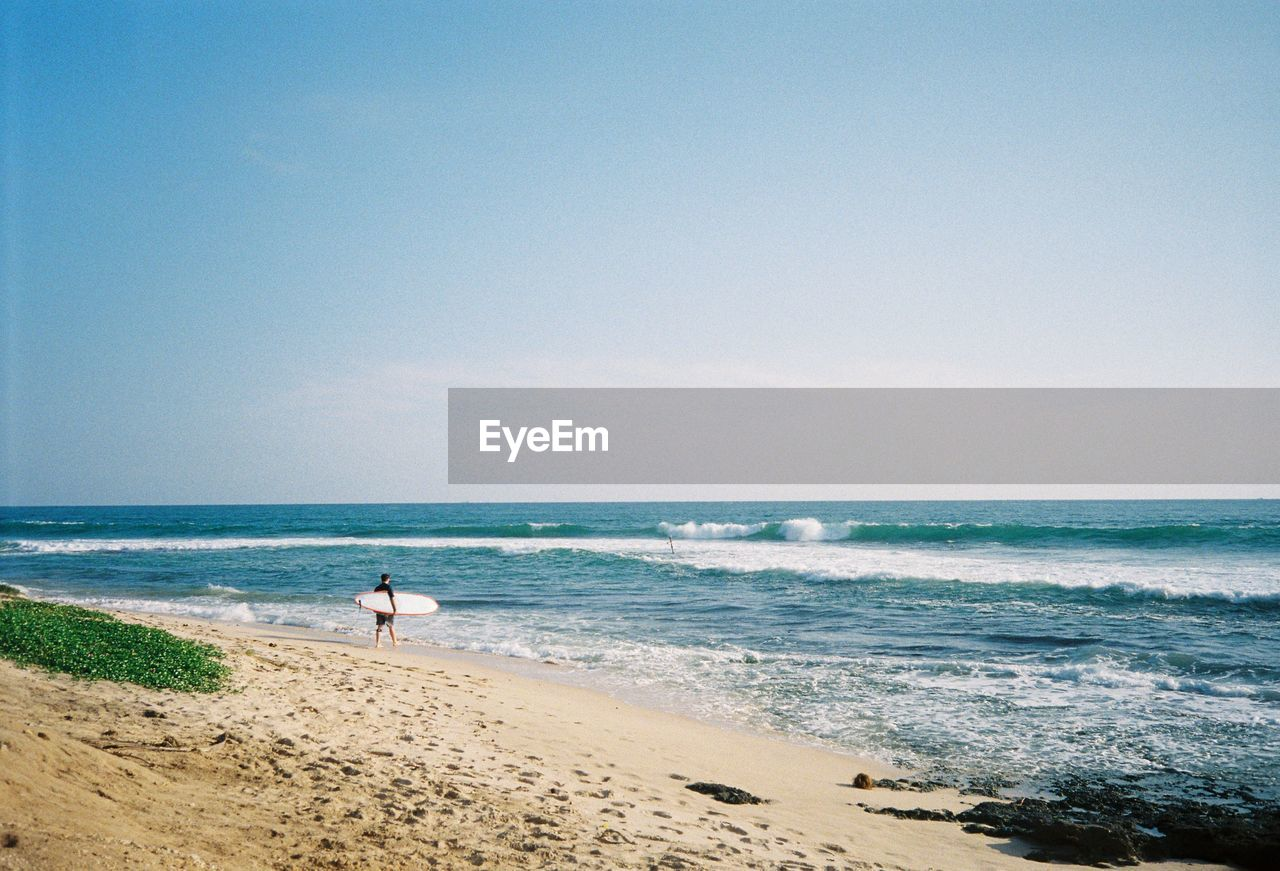 sea, horizon over water, beach, wave, water, shore, sand, beauty in nature, nature, scenics, sky, one person, clear sky, standing, real people, outdoors, day, vacations, tranquility, men, full length, one man only, people