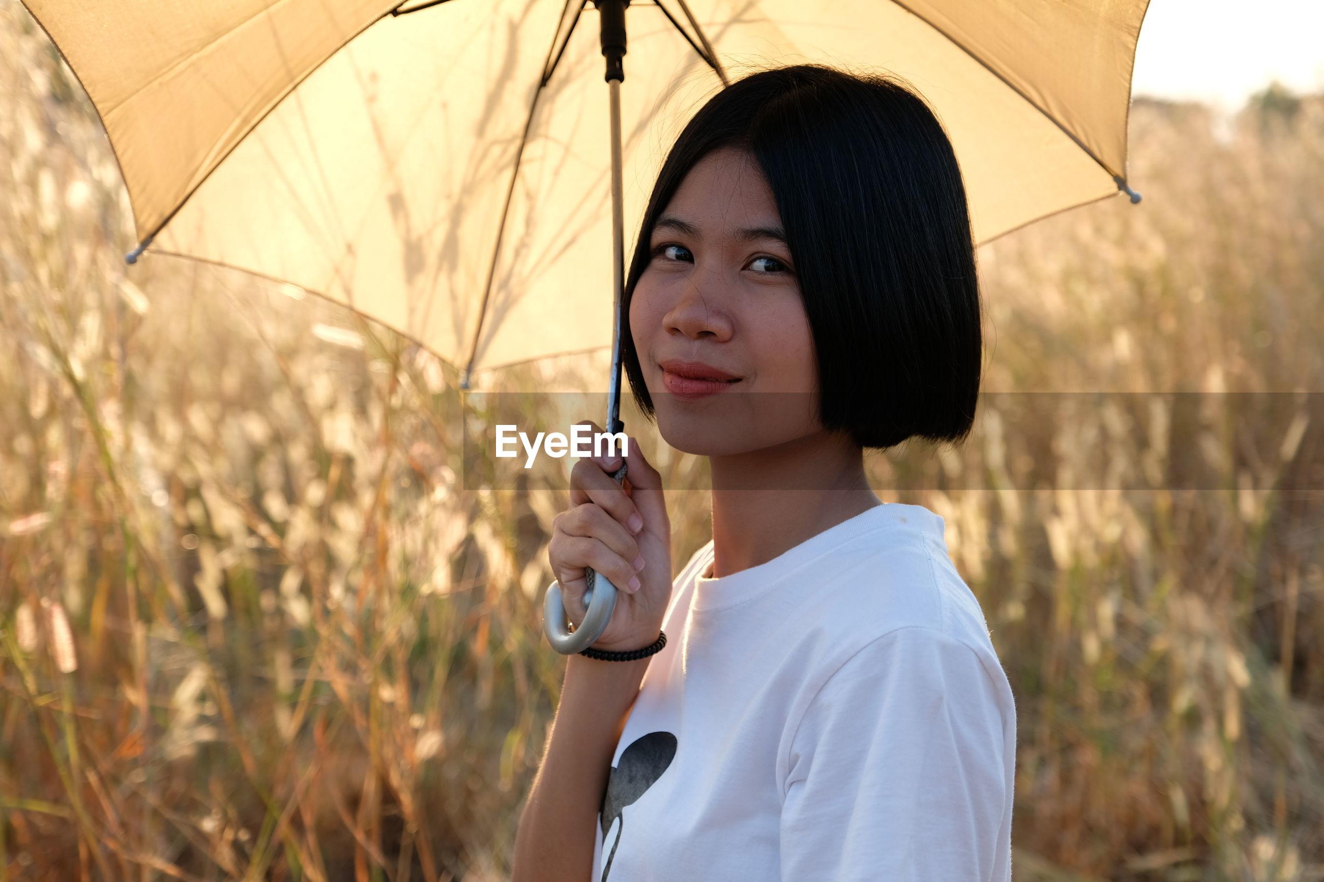 Portrait of woman holding umbrella against plants