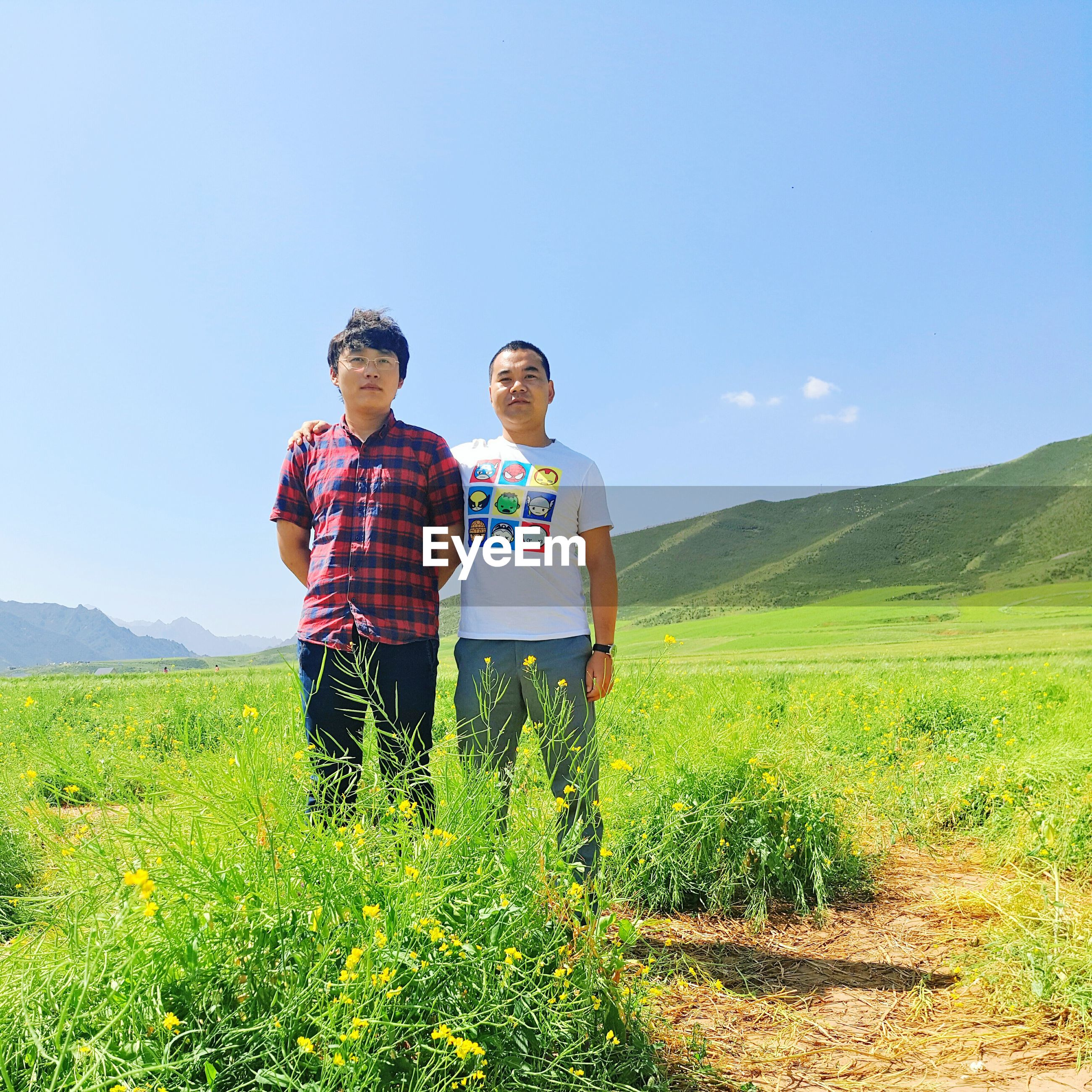 grass, standing, full length, leisure activity, casual clothing, young adult, hill, green color, plant, scenics, mountain, blue, beauty in nature, sky, person, nature, vacations, day, outdoors, carefree, grassy, tranquility, non-urban scene, memories