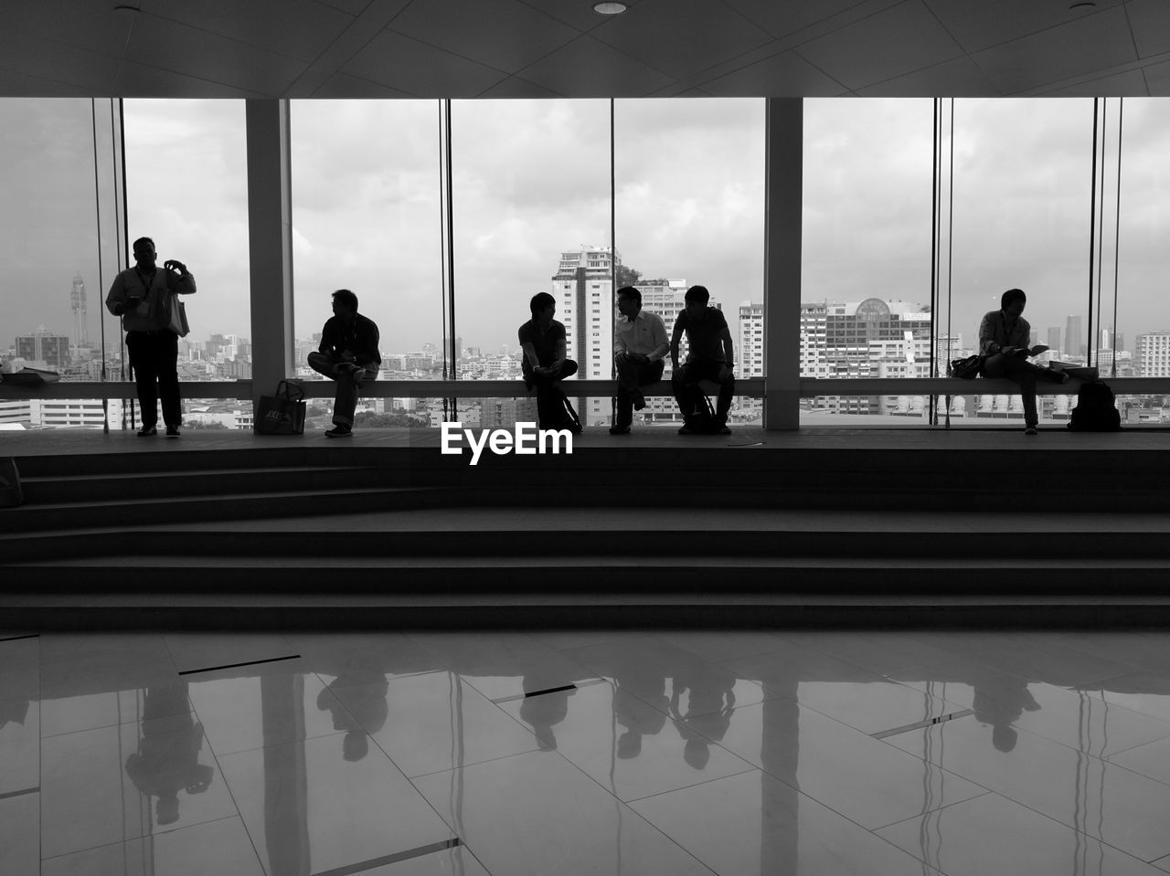 People Sitting On Benches In Modern Building