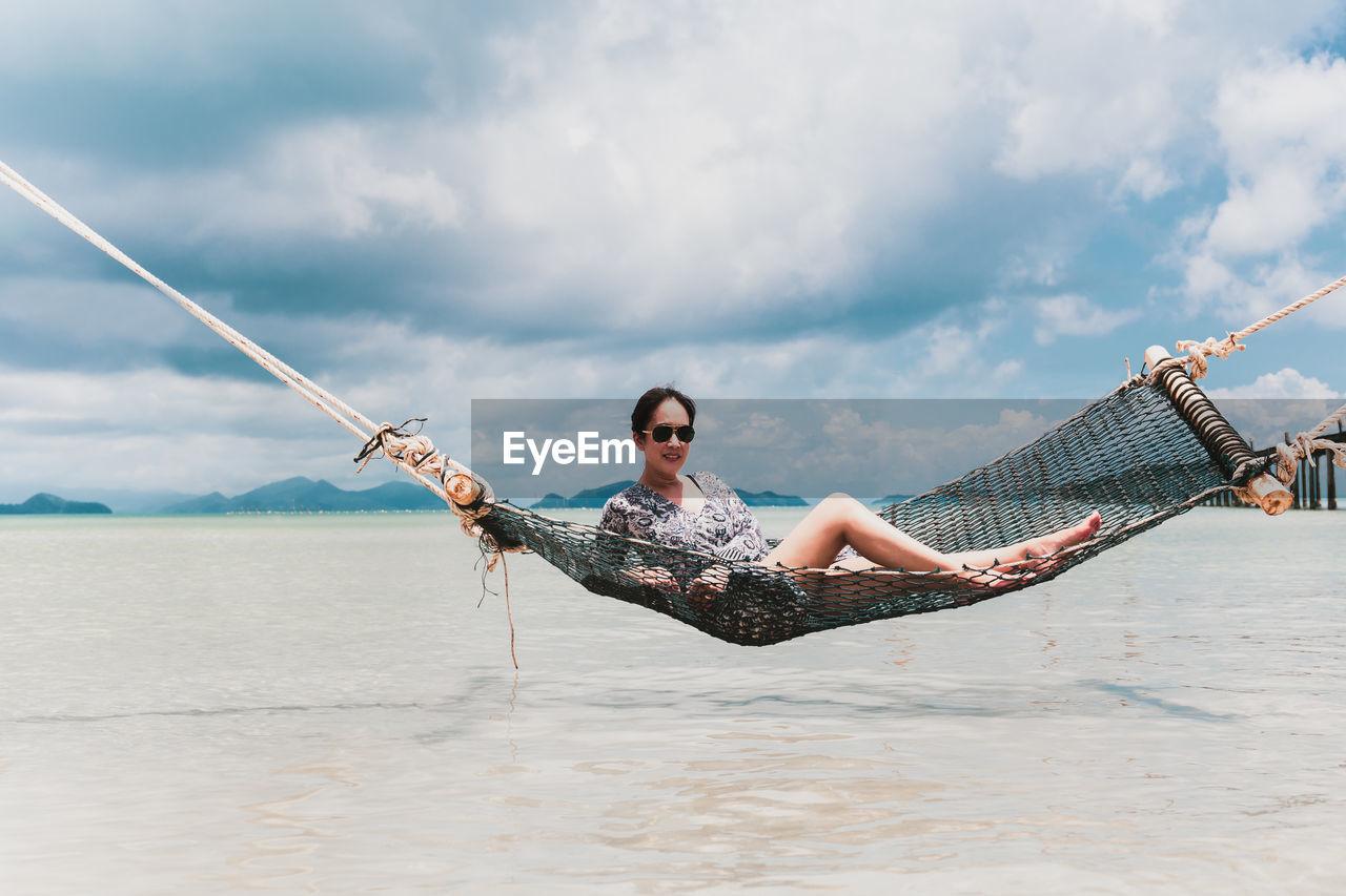 Woman relaxing in hammock on a beach against blue sky