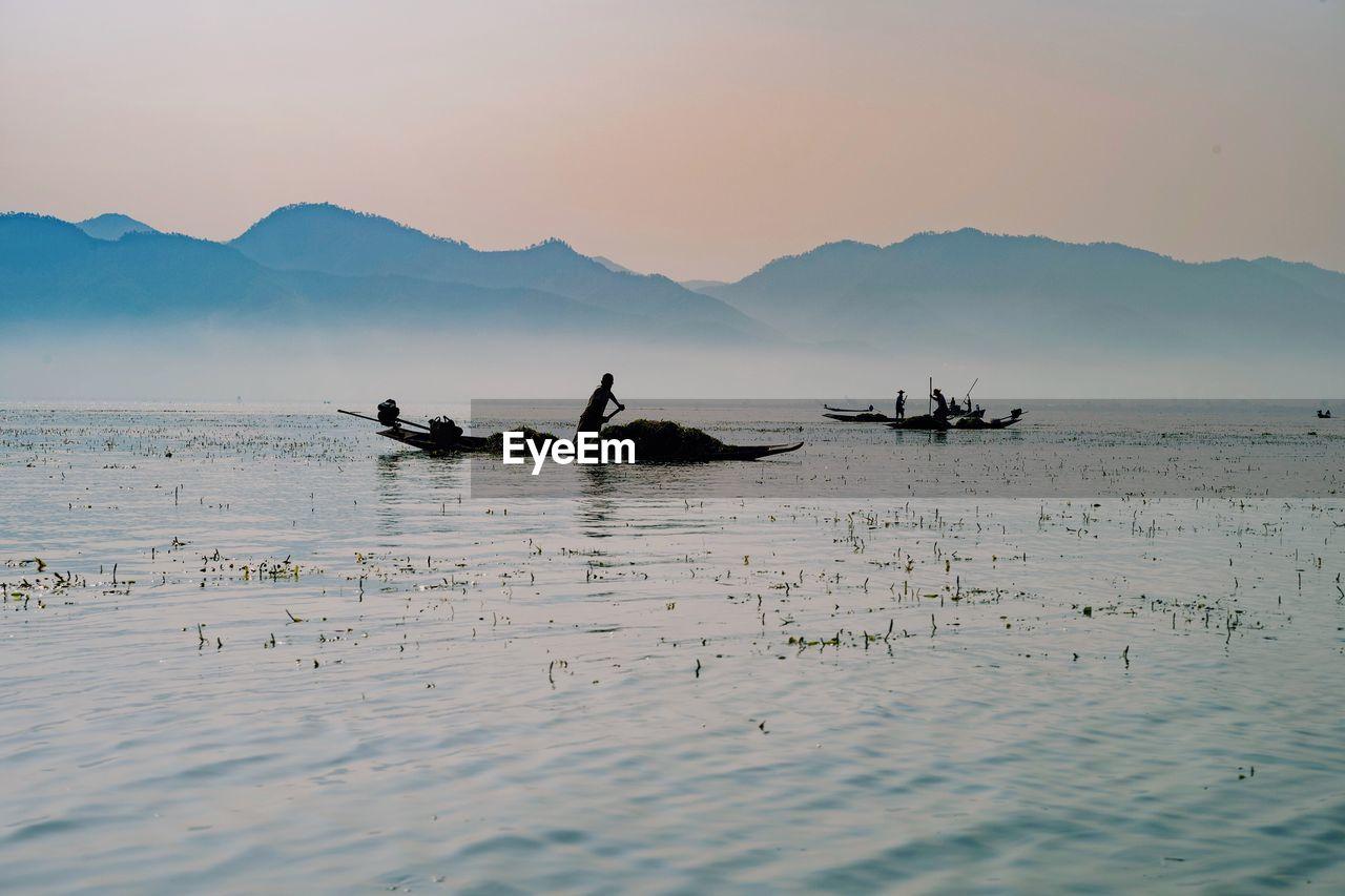 Silhouette of fishermen against sky during sunset