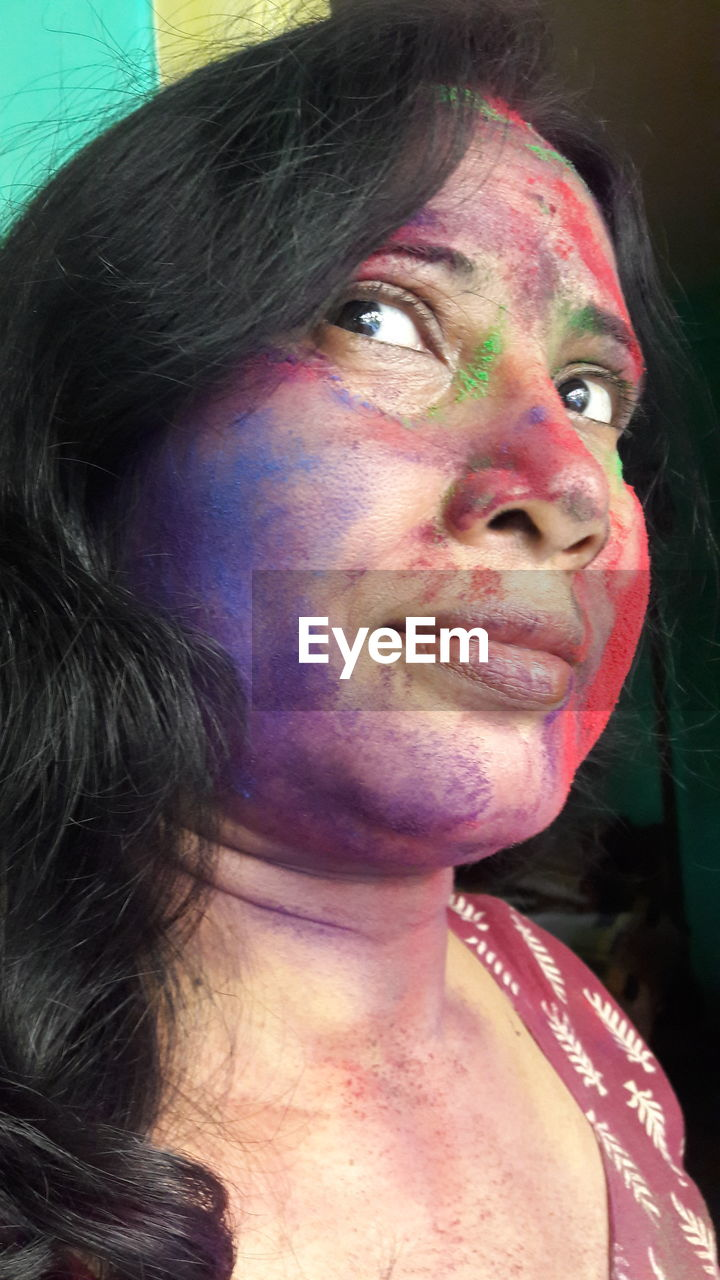 multi colored, real people, celebration, face paint, cultures, traditional festival, leisure activity, one person, lifestyles, holi, happiness, front view, headshot, human face, young women, young adult, portrait, close-up, powder paint, indoors, day