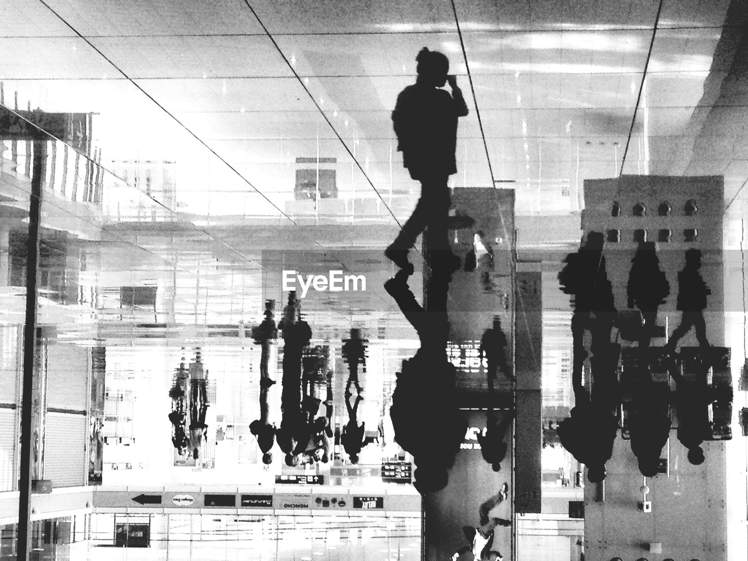 Upside down image of silhouette people on wet tiled floor