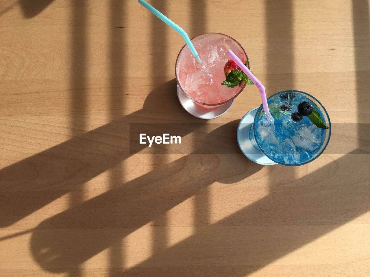 shadow, table, wood - material, sunlight, glass, food and drink, food, fruit, indoors, high angle view, drinking glass, refreshment, drinking straw, drink, no people, nature, straw, cocktail, household equipment, day, wood, herb, mint leaf - culinary, garnish