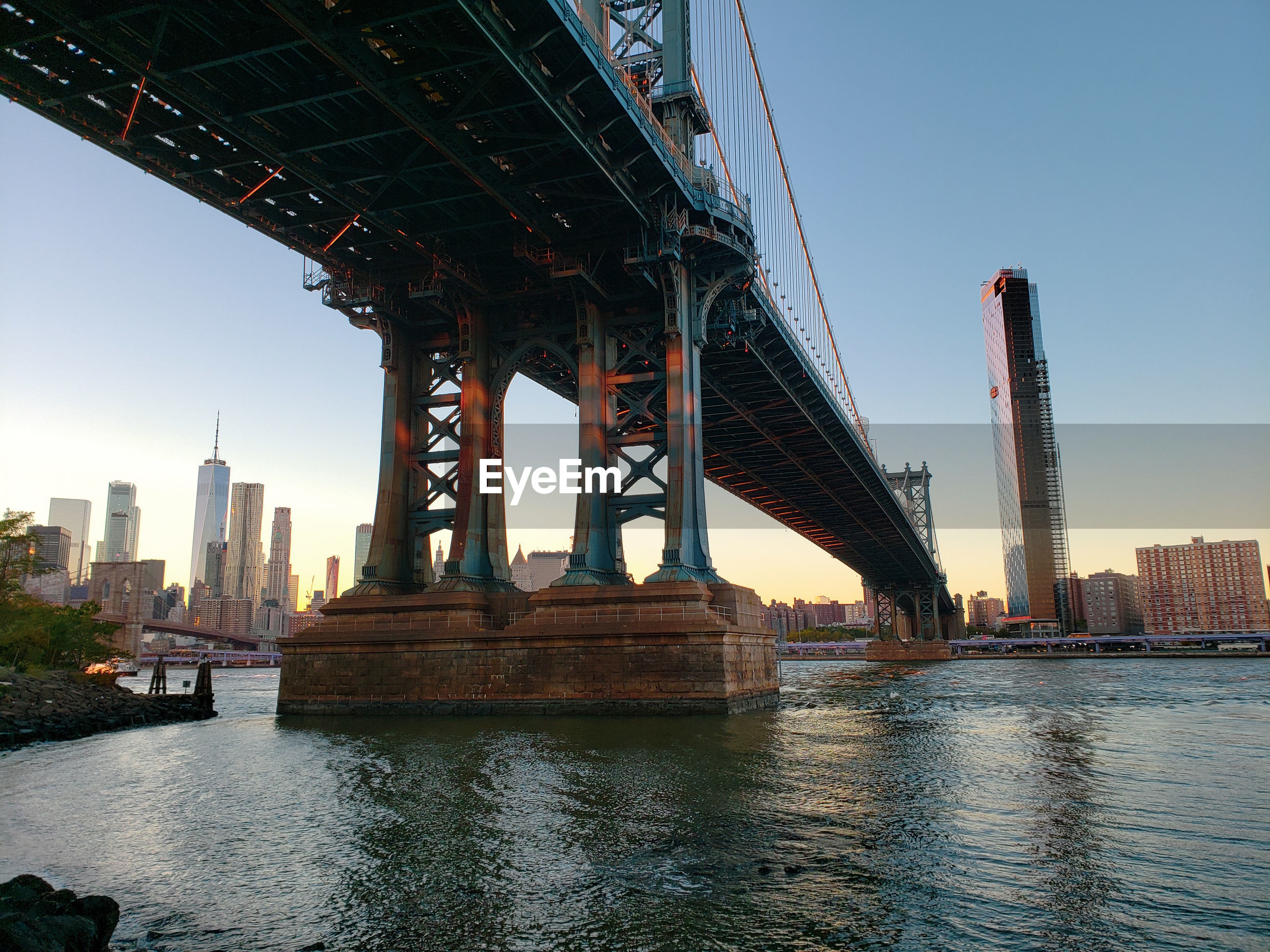 VIEW OF BRIDGE OVER RIVER AGAINST BUILDINGS