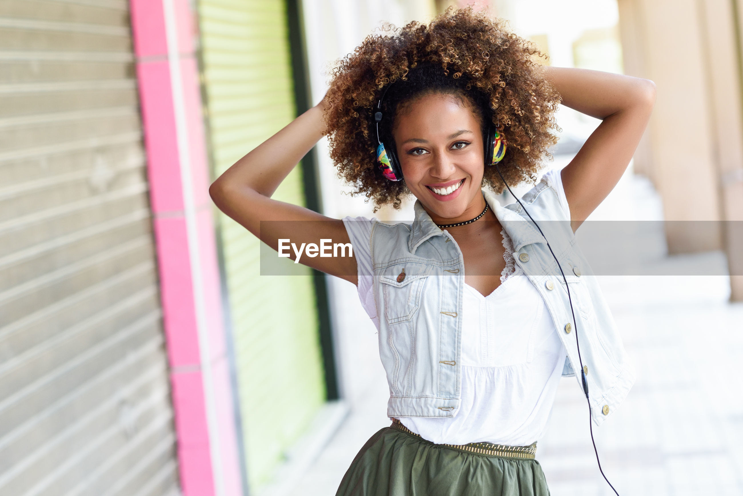Portrait of mid adult woman with curly hair standing outdoors