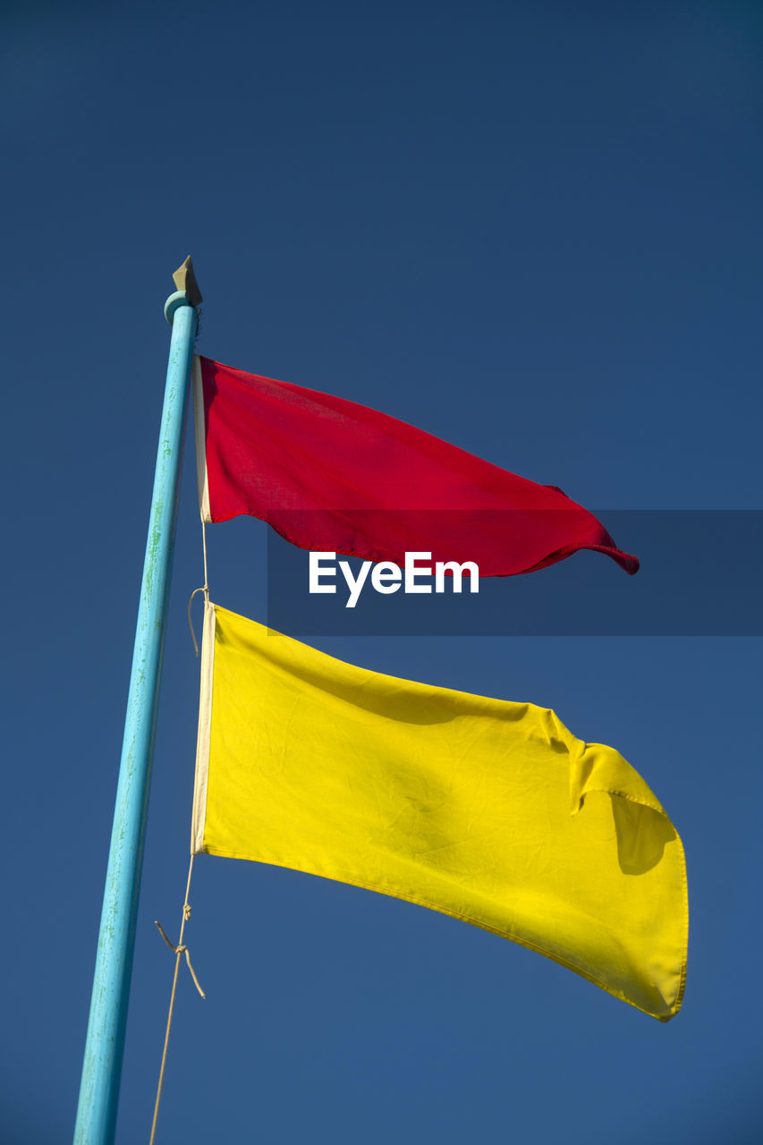 flag, yellow, low angle view, patriotism, blue, clear sky, red, day, outdoors, fluttering, no people, pride, sky