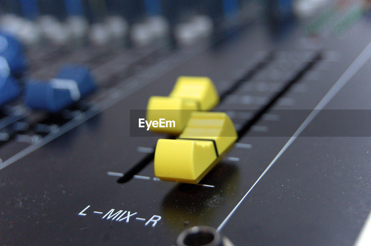technology, yellow, communication, computer, close-up, text, indoors, focus on foreground, connection, computer equipment, selective focus, western script, no people, computer part, control, control panel, sound recording equipment, high angle view, table, keyboard, push button, computer key