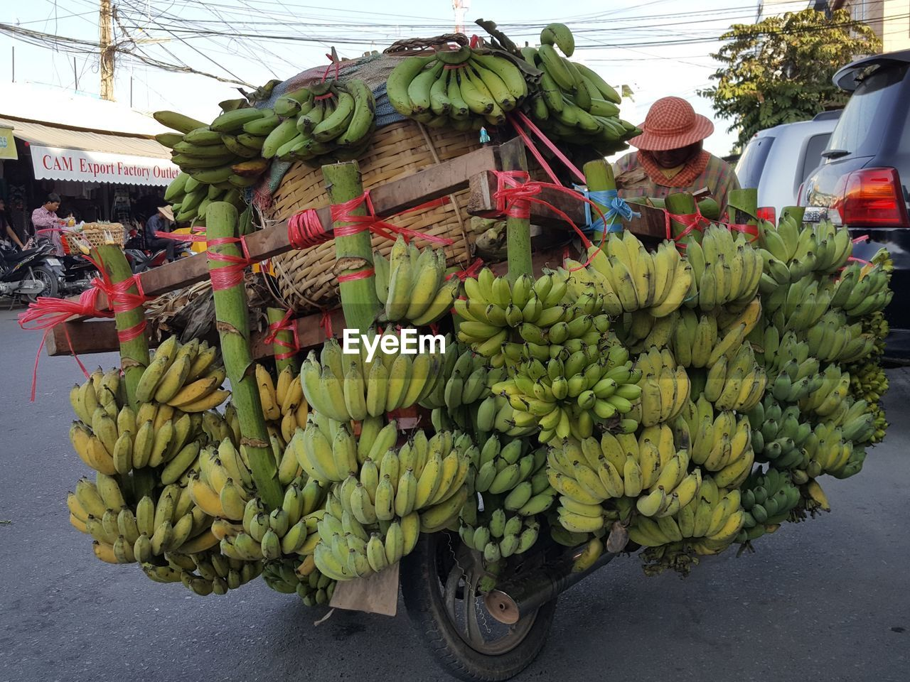 fruit, banana, food and drink, food, healthy eating, freshness, day, real people, vegetable, mode of transport, transportation, men, outdoors, banana tree, raw food, land vehicle, market, road, women, large group of people, people