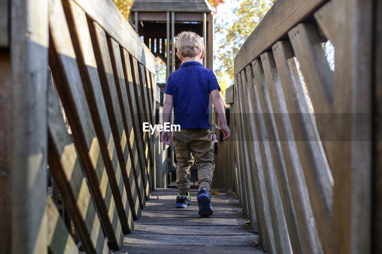 Rear view of boy walking on wooden footbridge