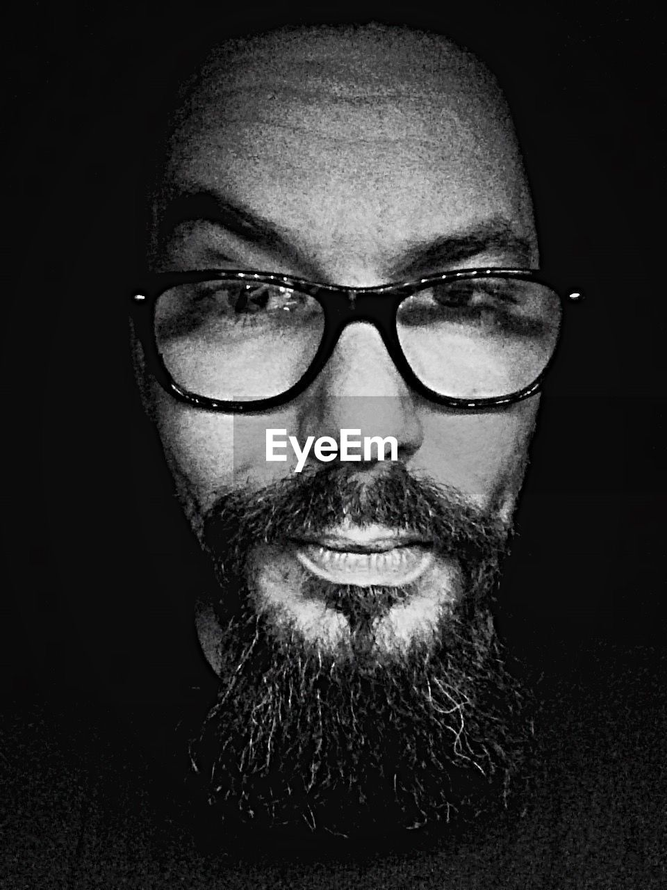 portrait, looking at camera, beard, eyeglasses, front view, one person, human face, black background, headshot, real people, one man only, young adult, only men, adults only, studio shot, close-up, men, adult, indoors, people, day