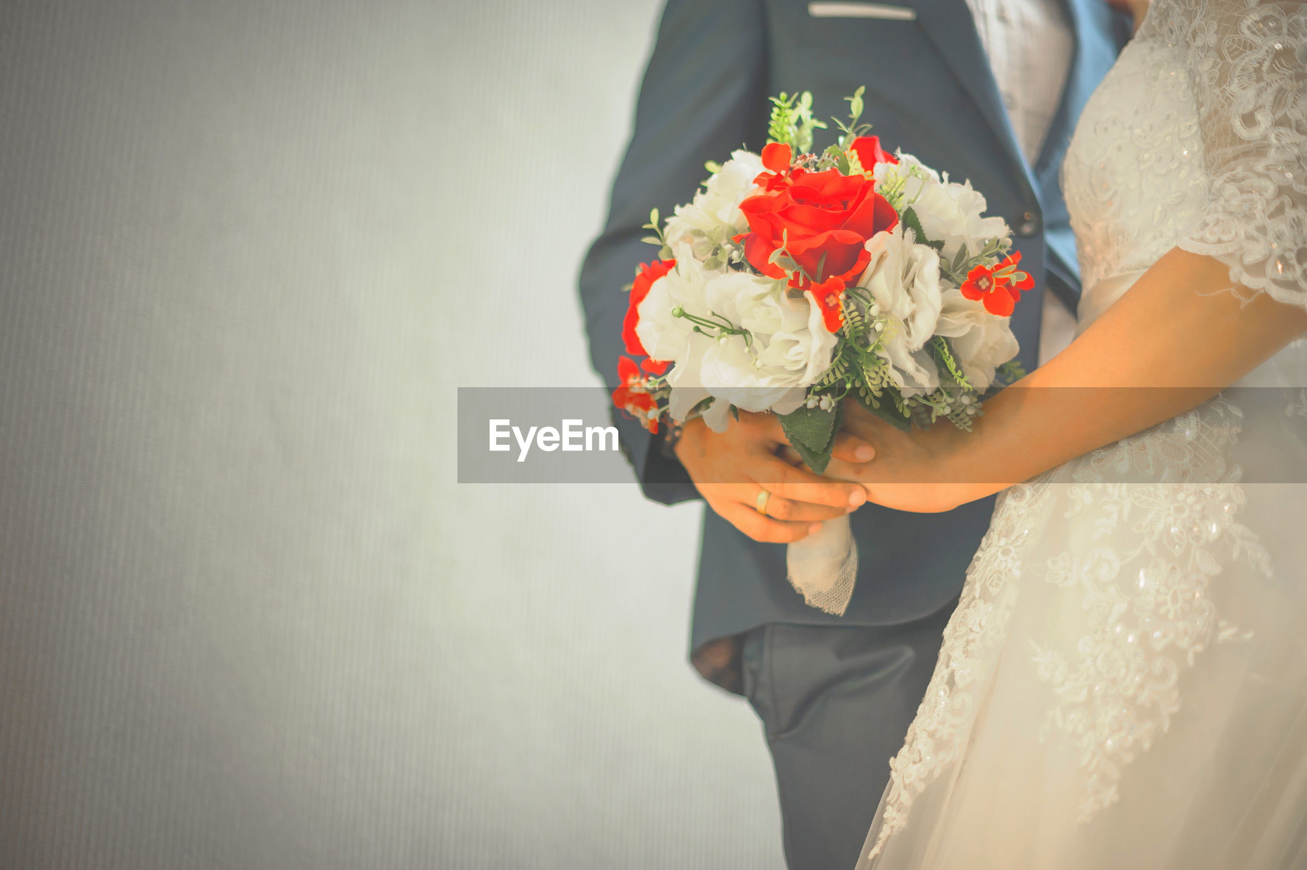 Midsection of bride and groom holding bouquet against white wall