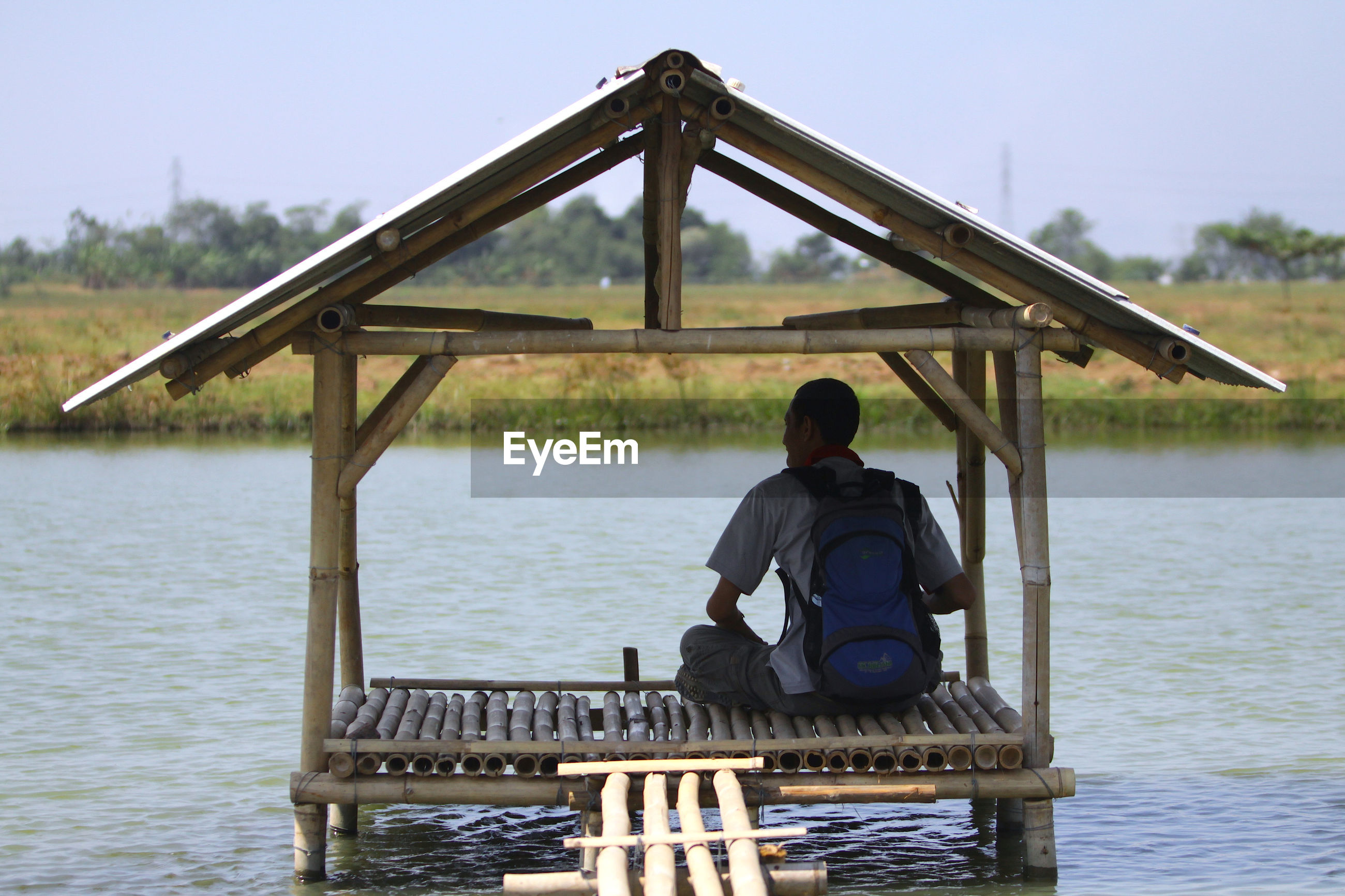 Rear view of man sitting on built structure in river against sky