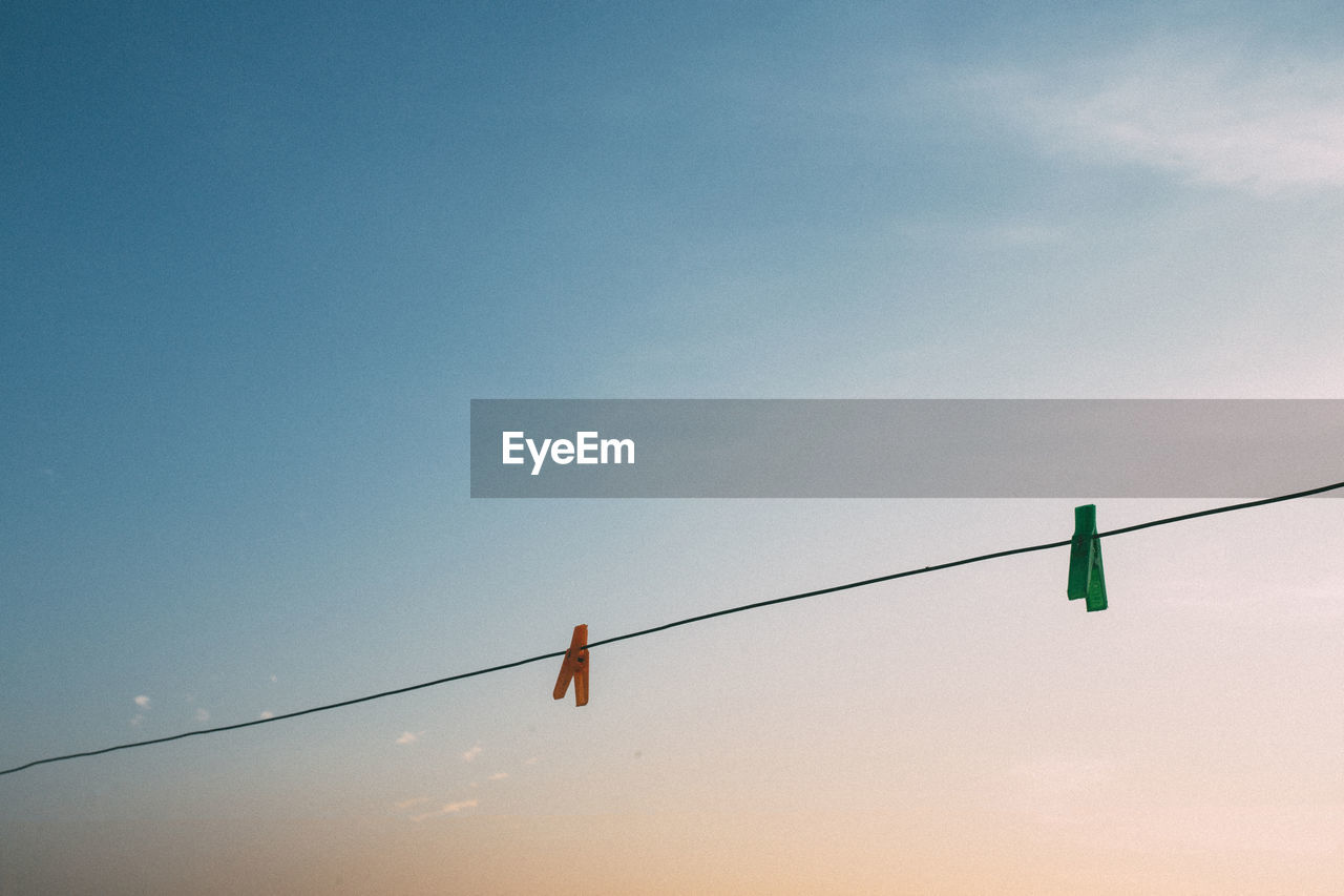 Low Angle View Of Clothespin Hanging On Rope Against Sky During Sunset