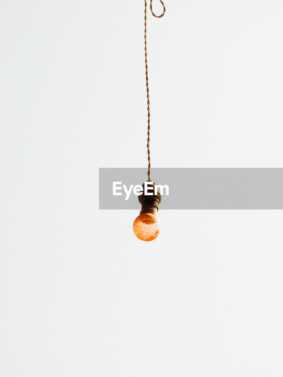 Low angle view of lighting equipment hanging against white background