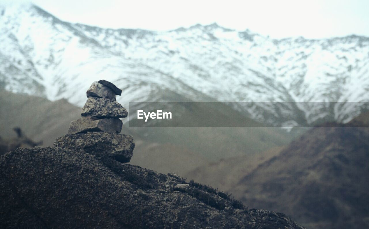 Stack Of Stones Against Snowcapped Mountain