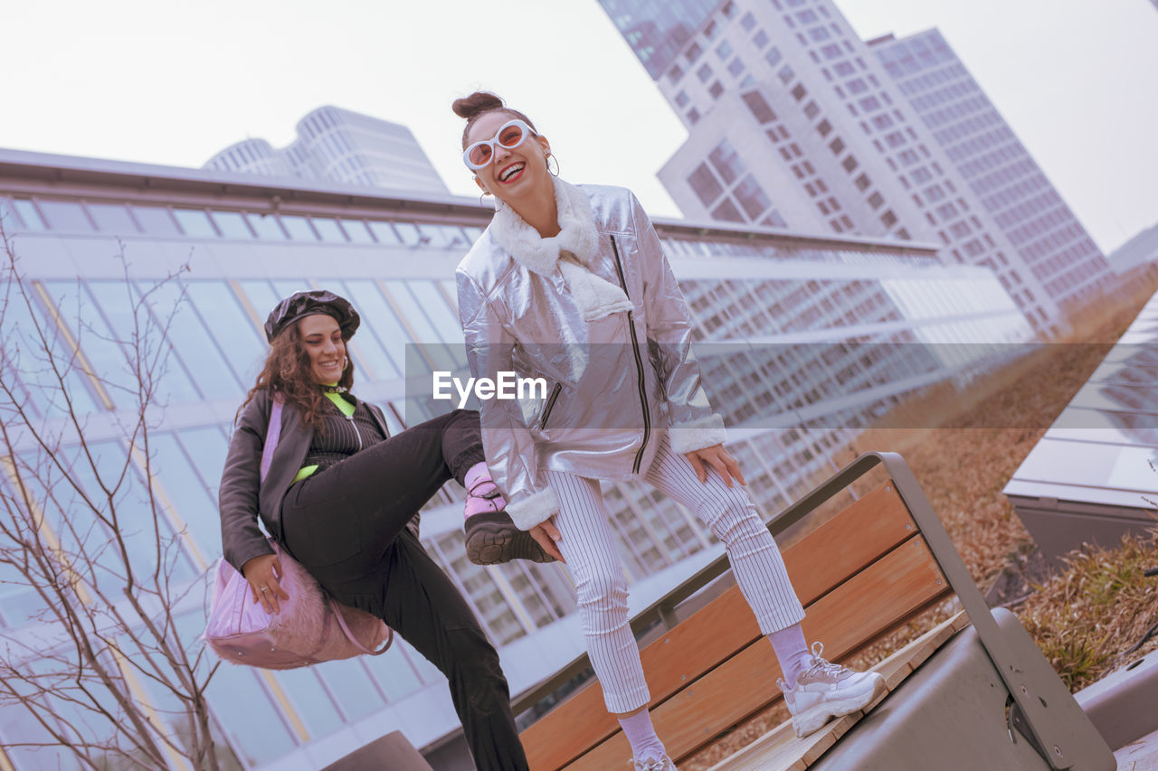 architecture, real people, built structure, young women, building exterior, emotion, two people, adult, young adult, full length, people, happiness, women, casual clothing, smiling, sitting, lifestyles, young men, leisure activity