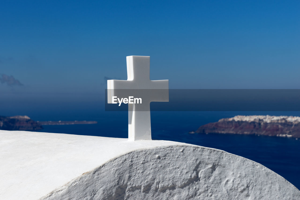 cross, religion, belief, spirituality, sky, no people, blue, water, nature, day, solid, architecture, white color, outdoors, sea, symbol, sunlight, grave