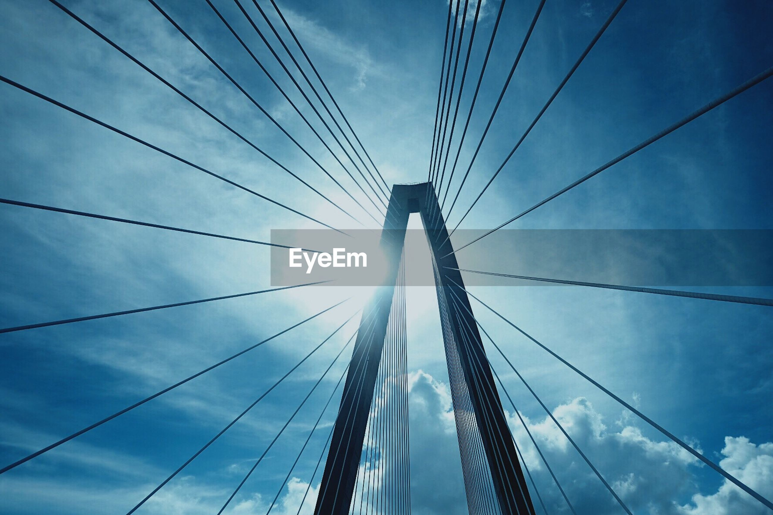connection, low angle view, engineering, architecture, sky, built structure, suspension bridge, cable, transportation, bridge - man made structure, cloud - sky, outdoors, day, modern, blue, no people, skyscraper, building exterior, city