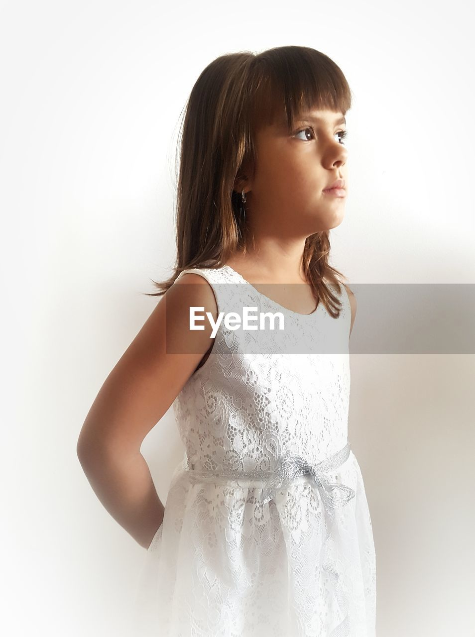 Close-up of girl in dress standing against white background