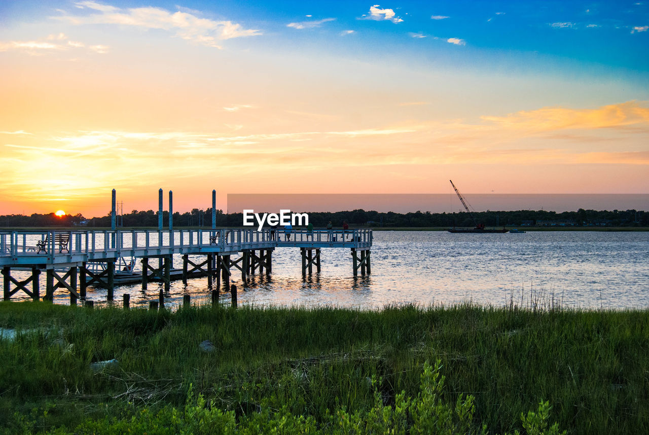 sunset, tranquil scene, water, nature, scenics, beauty in nature, sky, tranquility, grass, sea, cloud - sky, built structure, outdoors, wooden post, travel destinations, no people, architecture, day