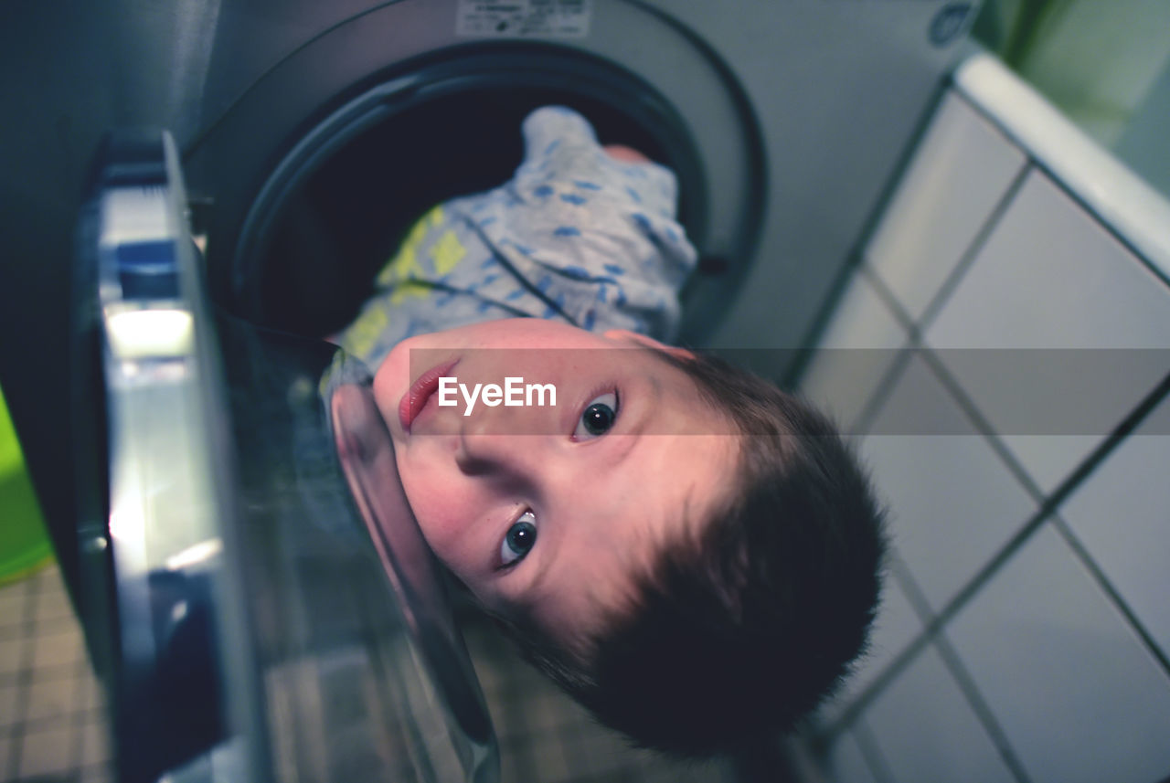 High Angle Portrait Of Boy In Washing Machine