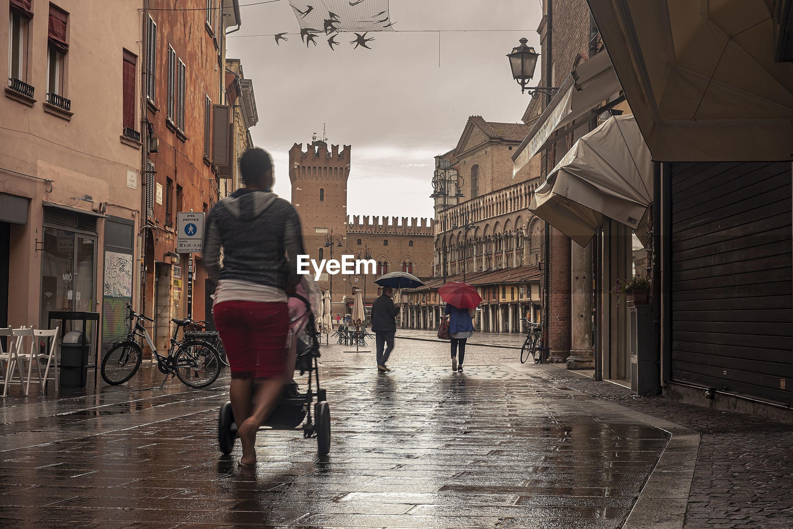 REAR VIEW OF PEOPLE WALKING ON WET STREET IN CITY