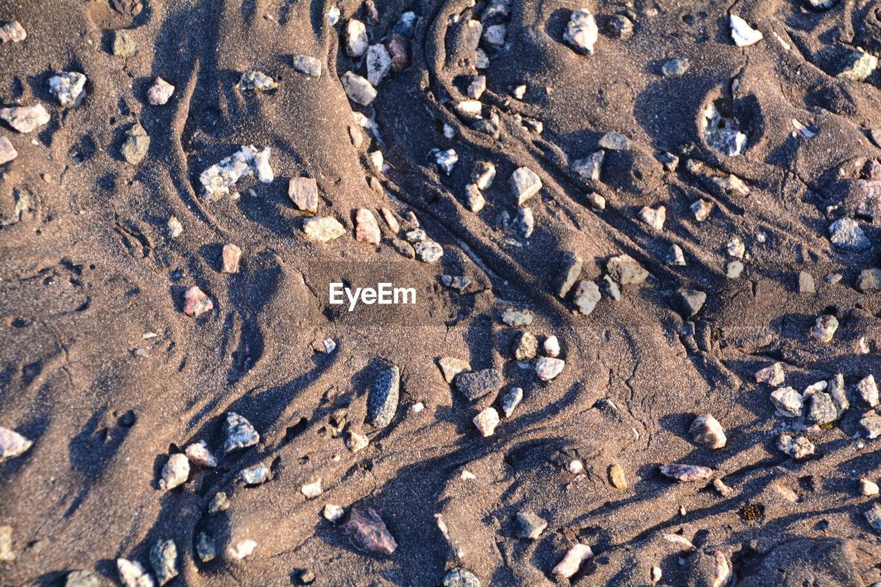 Full Frame Shot Of Pebbles On Sand At Beach
