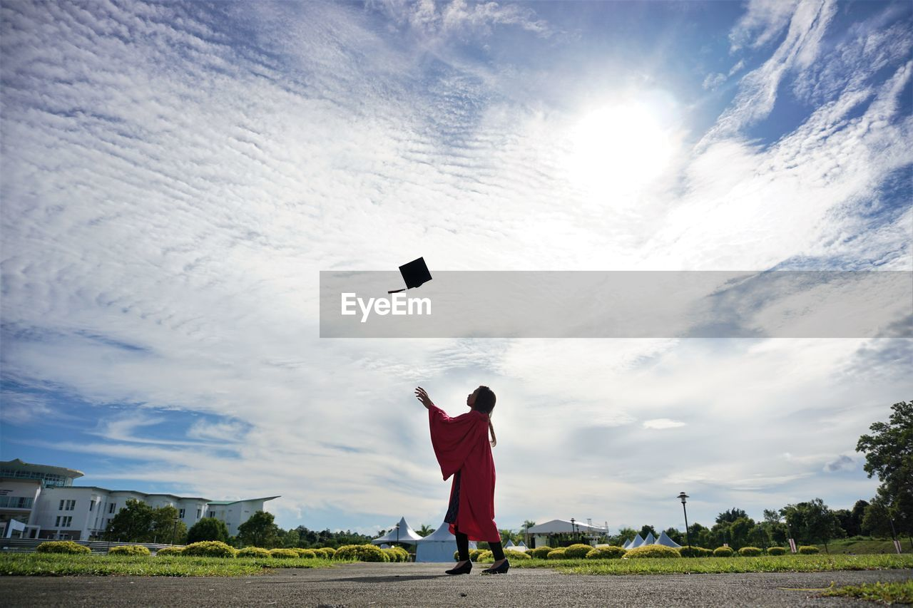 Side View Of University Student Throwing Mortarboard Against Sky During Graduation