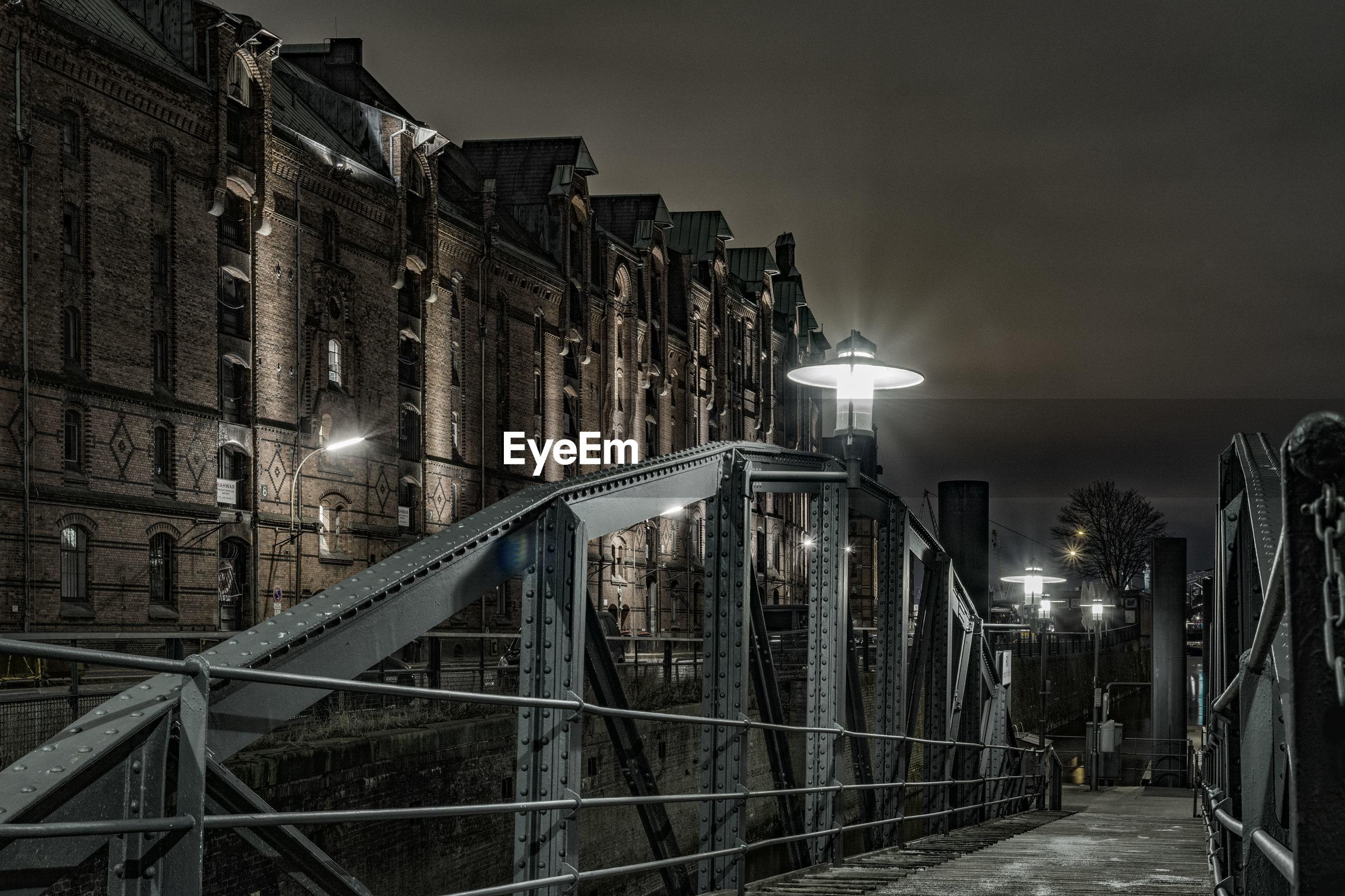 Footbridge by building at night