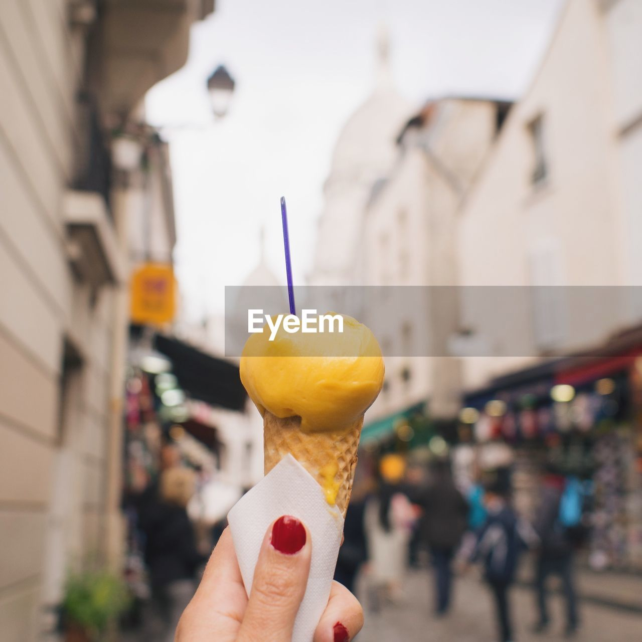 Cropped Image Of Woman Hand Holding Ice Cream Cone On Street In City