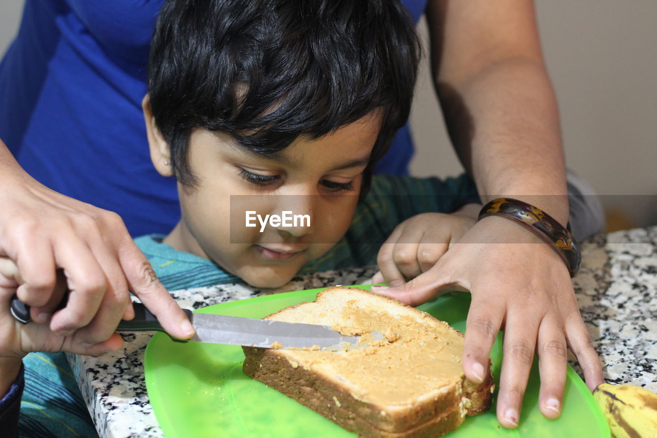 Cropped Image Of Mother And Son Preparing Food