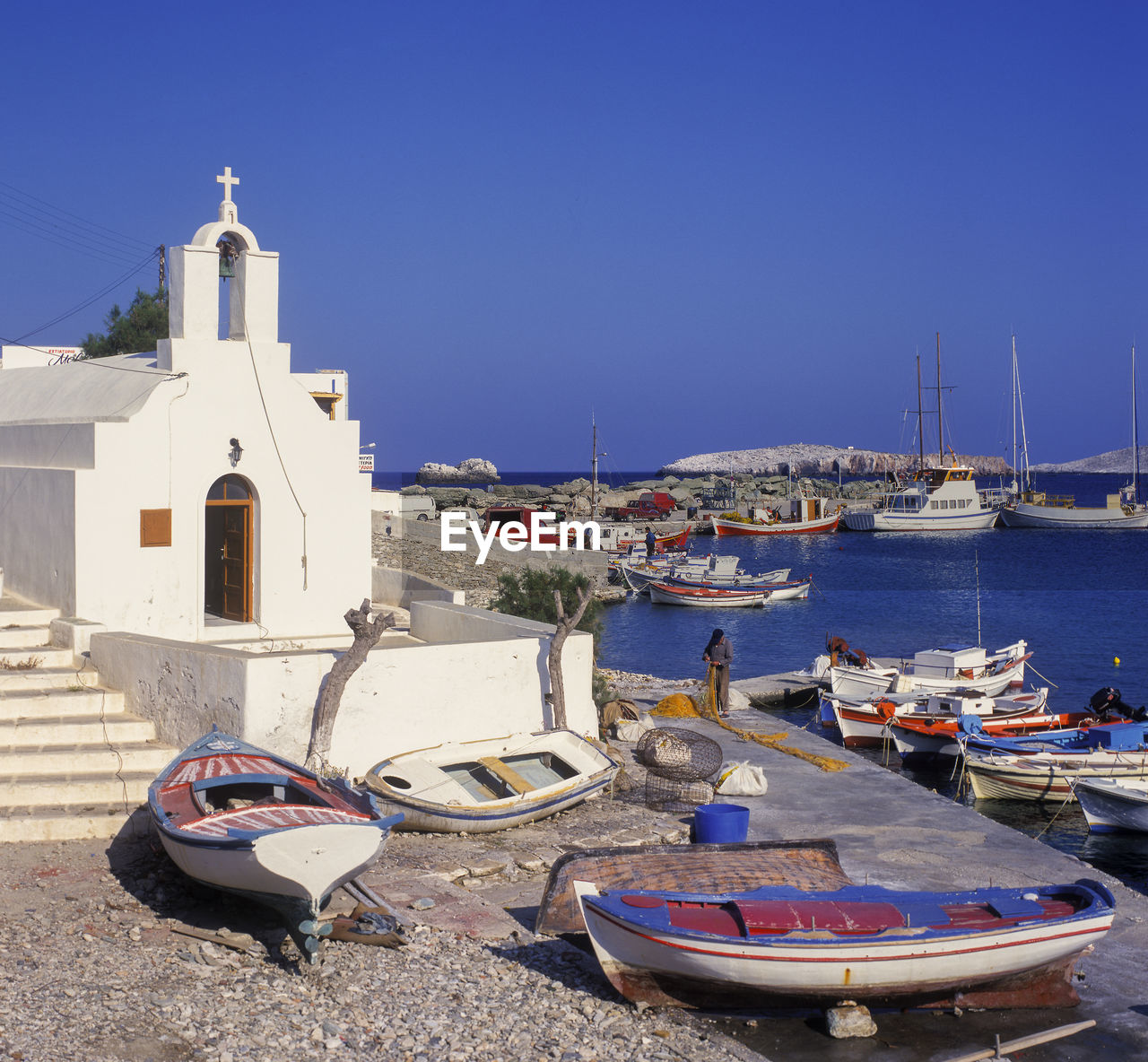 Church By Boats Moored At Harbor During Sunny Day