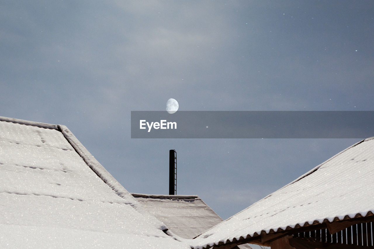 Low Angle View Of Snow Covered Roof Against Sky