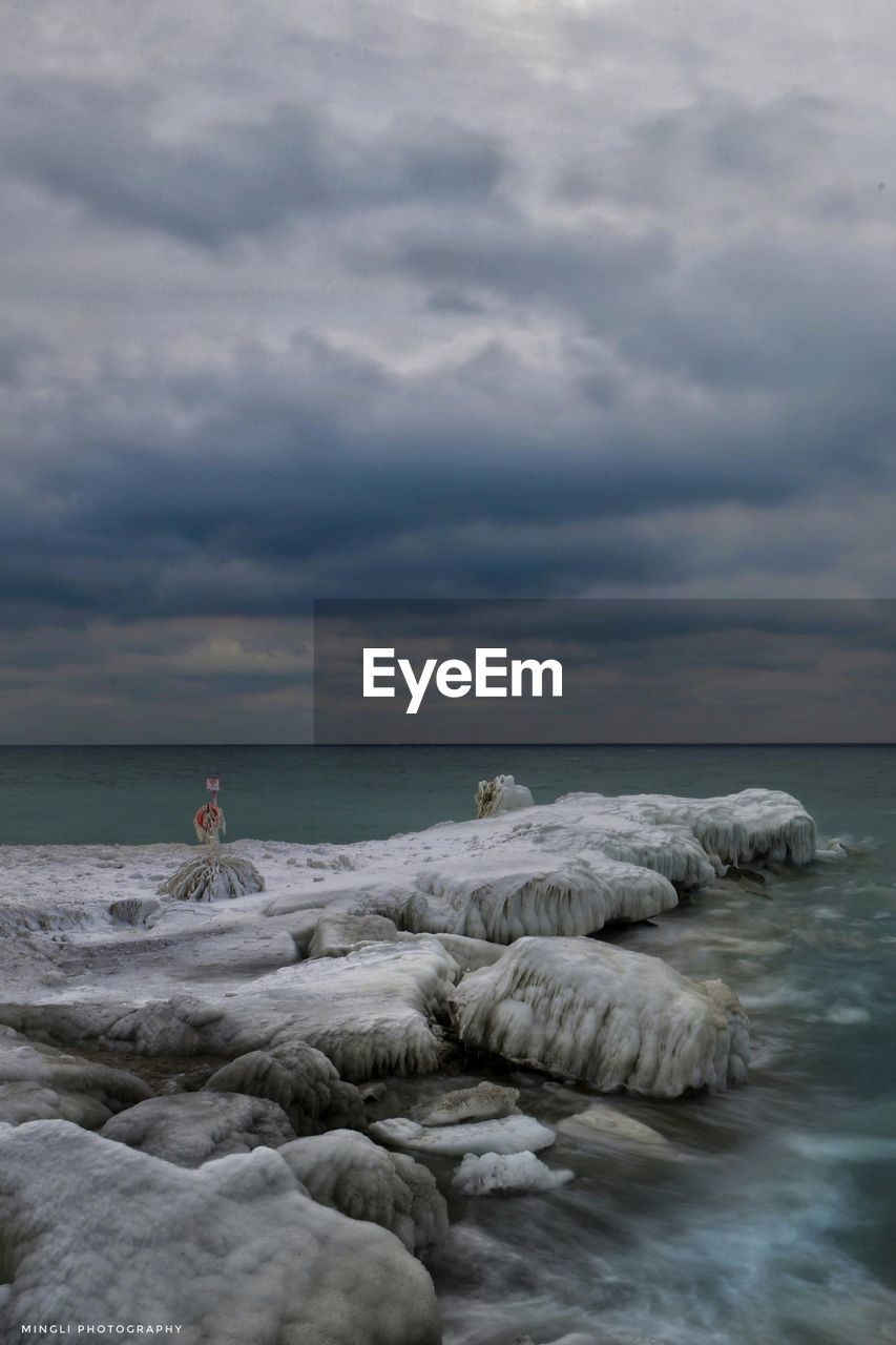 cloud - sky, sky, sea, water, horizon over water, horizon, scenics - nature, beauty in nature, nature, land, tranquility, tranquil scene, rock, beach, solid, overcast, rock - object, people