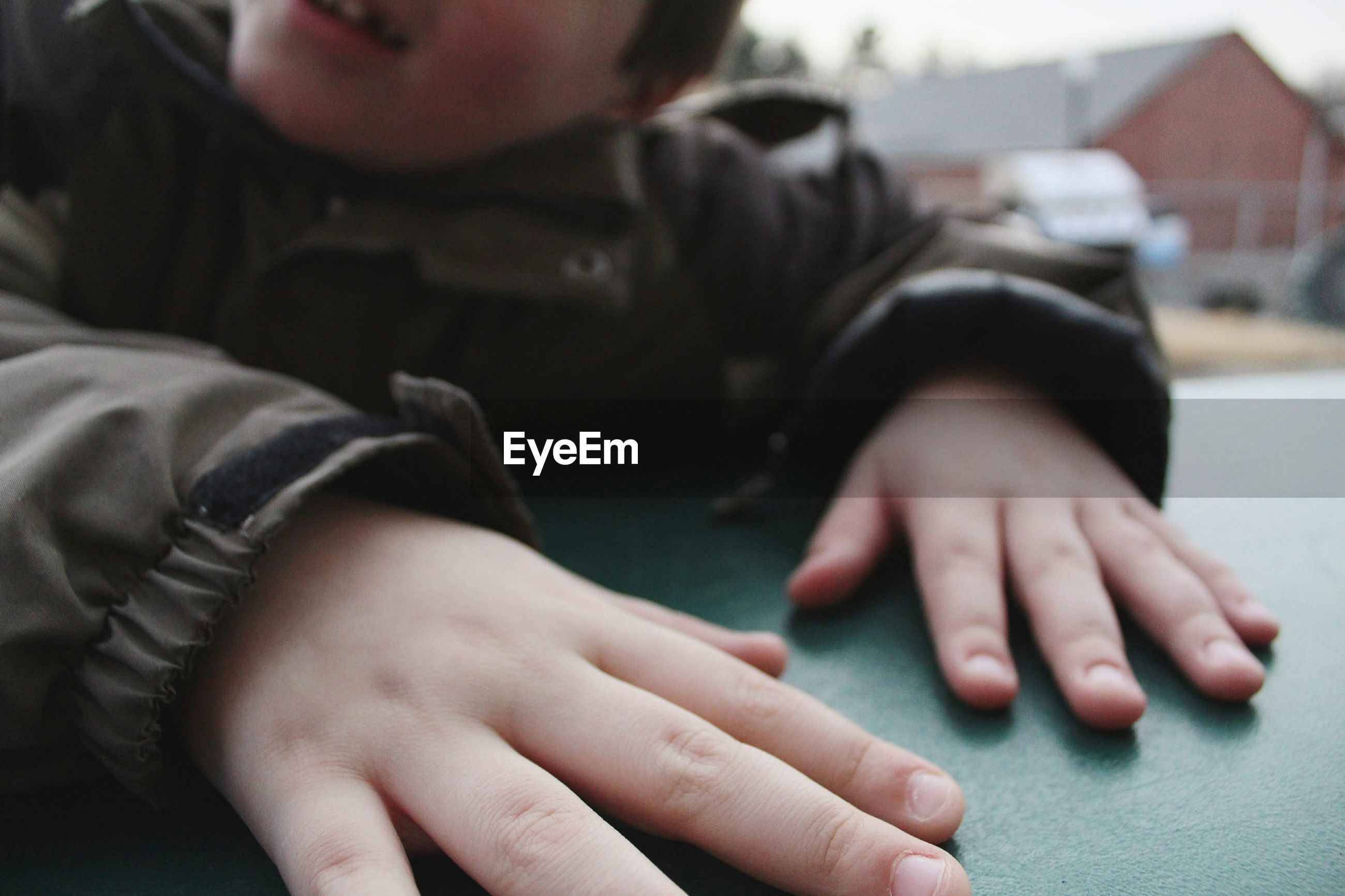 Midsection of boy with hands on table