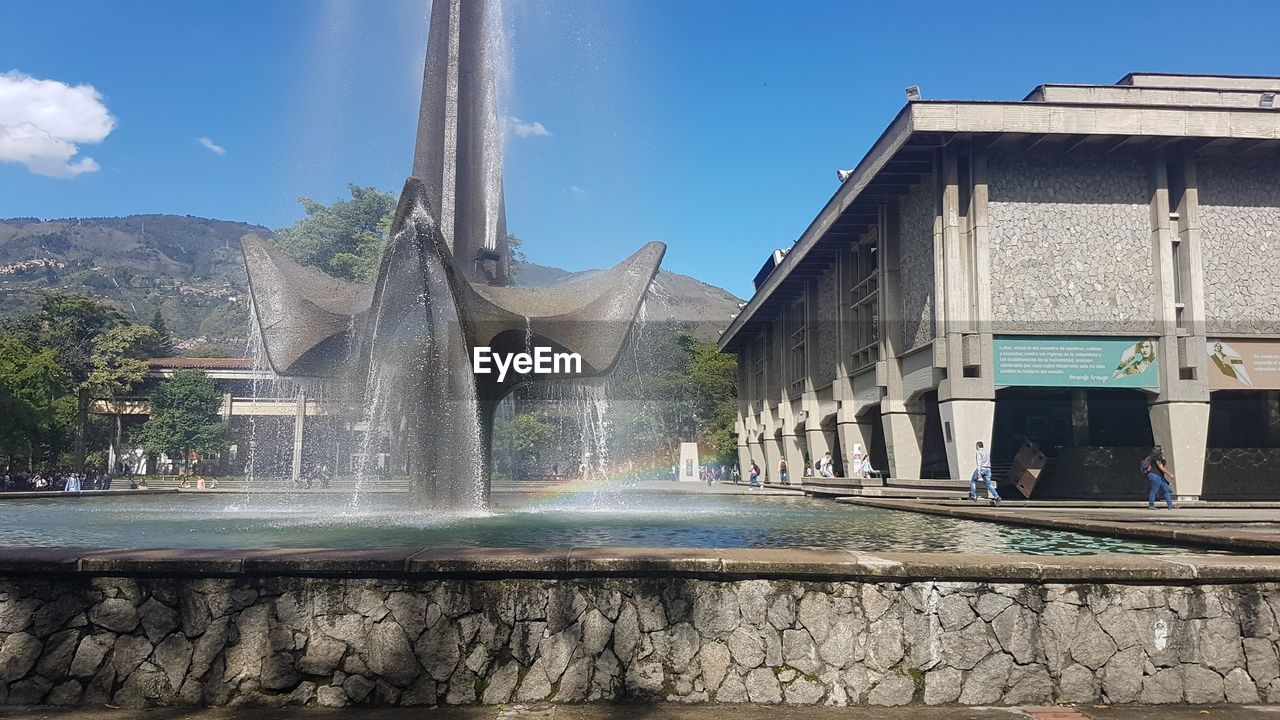 architecture, built structure, water, sky, building exterior, fountain, motion, nature, day, spraying, building, long exposure, sunlight, incidental people, travel destinations, outdoors, blue, splashing, flowing water, flowing