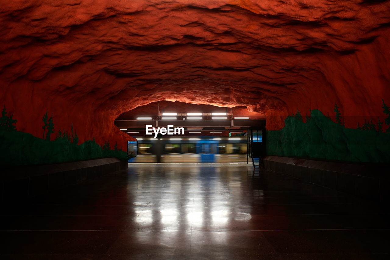 illuminated, indoors, architecture, the way forward, no people, direction, built structure, empty, tunnel, flooring, night, lighting equipment, public transportation, subway, electric light, absence, transportation, light, cave, ceiling, underpass