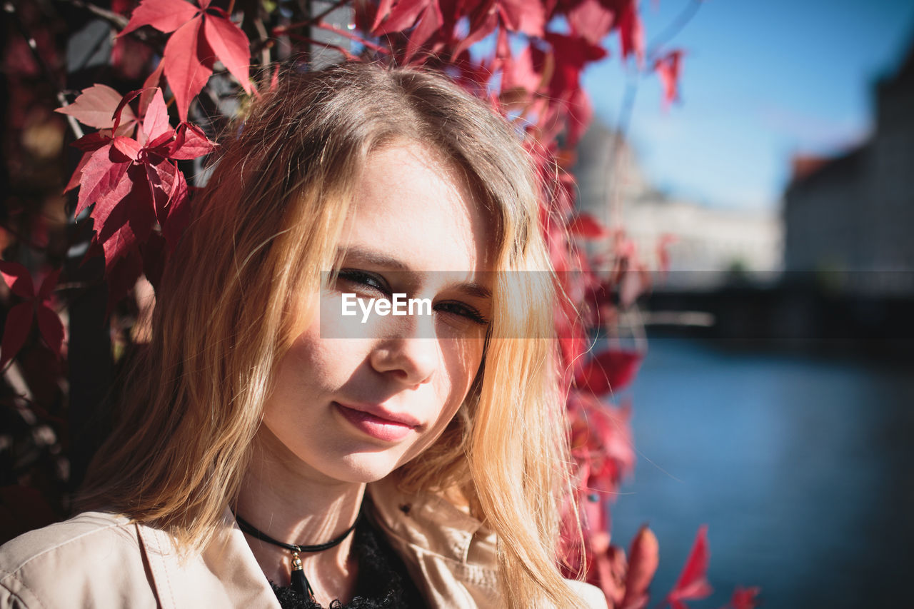 Close-Up Portrait Of Young Woman By Plants