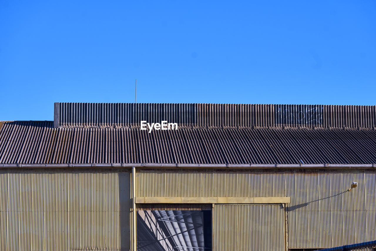 sky, architecture, built structure, building exterior, clear sky, blue, roof, building, day, copy space, nature, no people, low angle view, corrugated iron, corrugated, sunlight, industry, iron, factory, outdoors