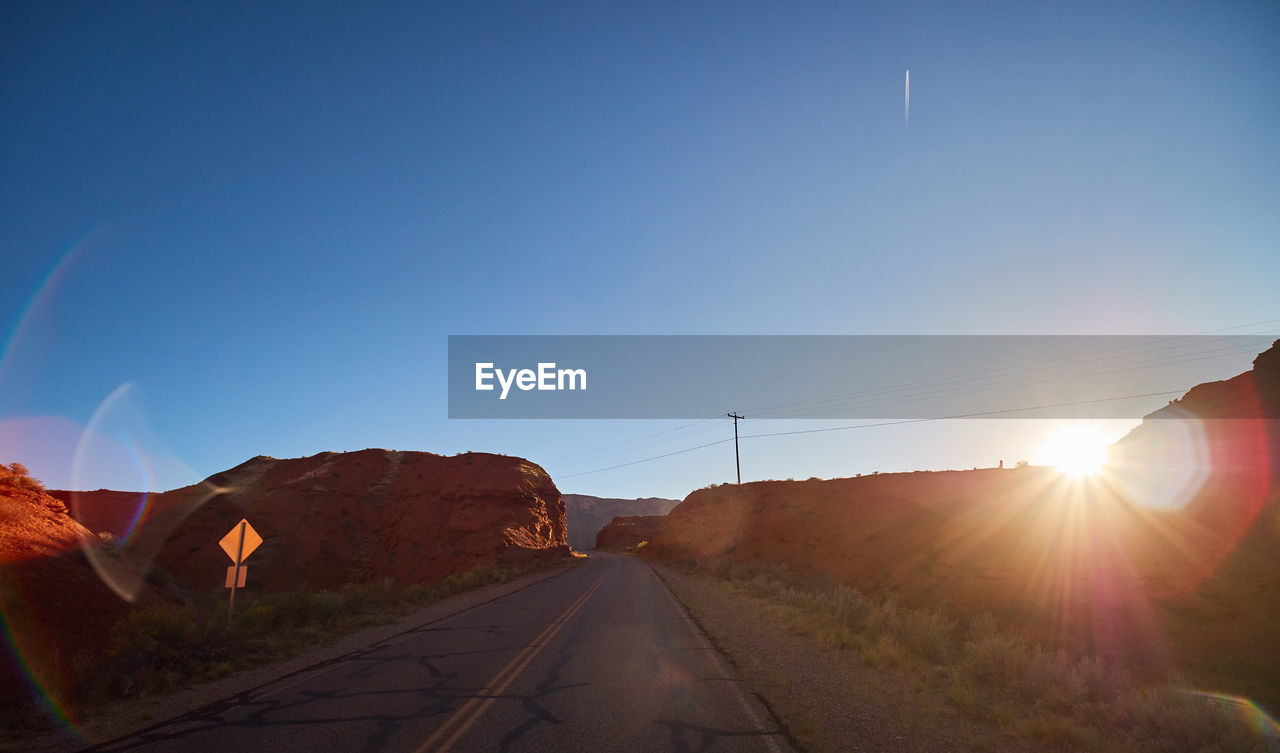 sky, transportation, nature, road, sunlight, sun, lens flare, direction, the way forward, mountain, sunbeam, beauty in nature, no people, clear sky, mode of transportation, environment, scenics - nature, sunset, landscape, tranquil scene, outdoors, diminishing perspective, bright
